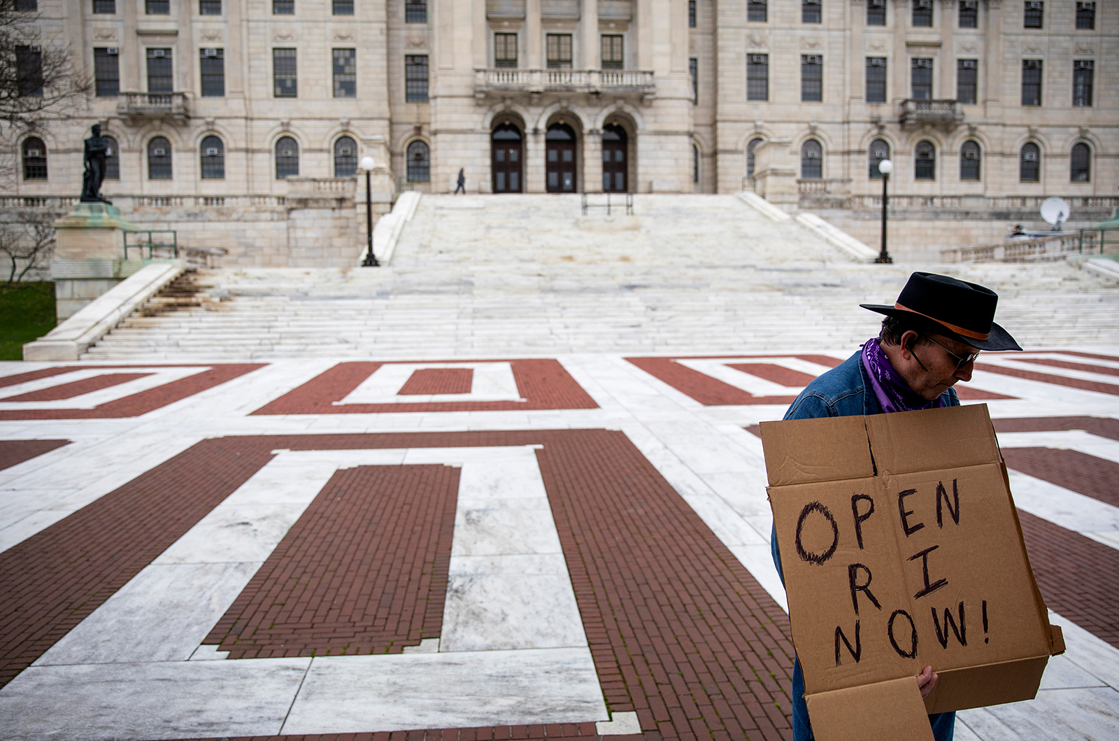 James Dunn stands outside the Statehouse with a handmade sign in favor of reopening the state economy as Rhode Island Gov. Gina Raimondo delivers her daily briefing inside, on Friday, May 1, in Providence.