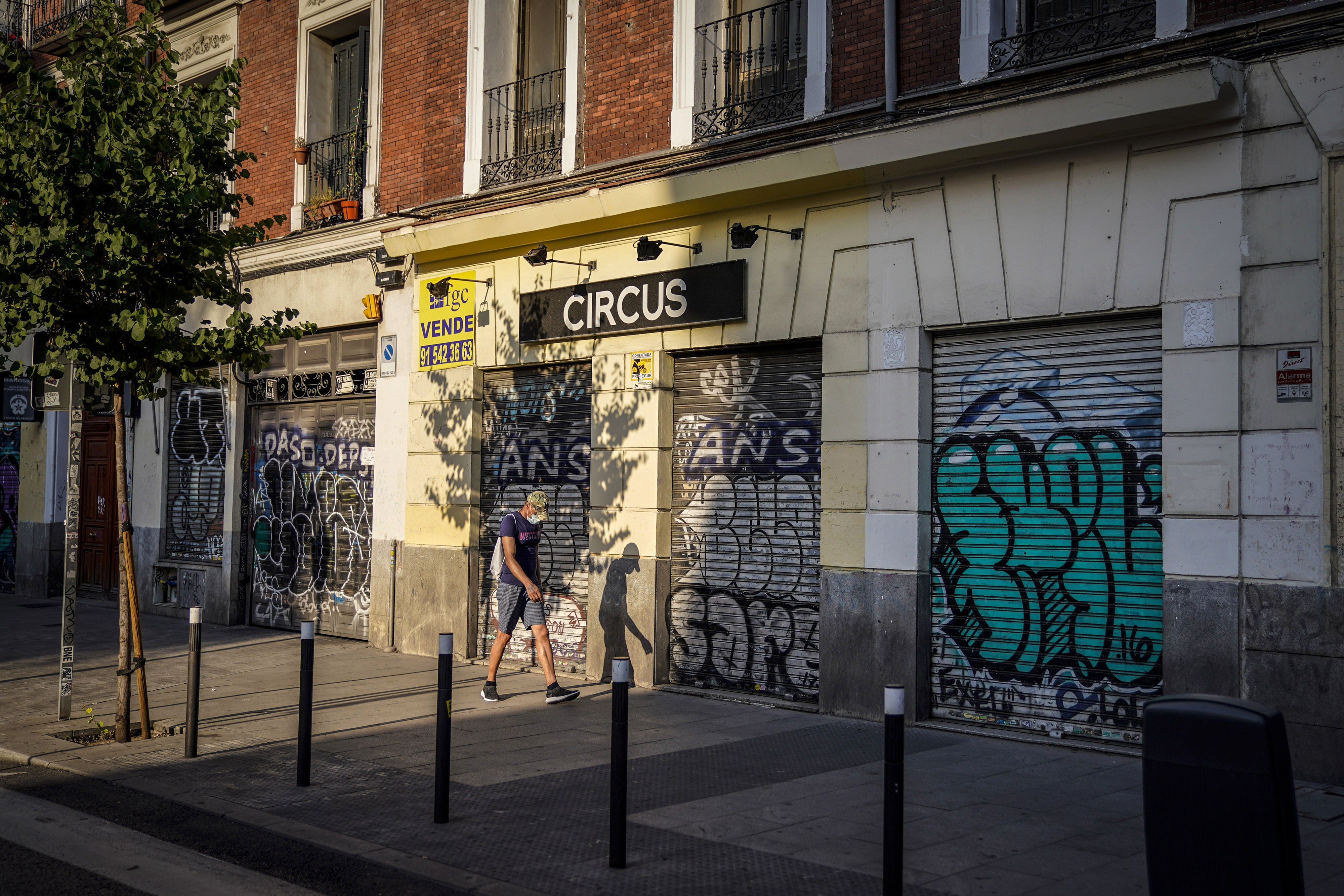 A person walks past shuttered businesses in Madrid on July 24.