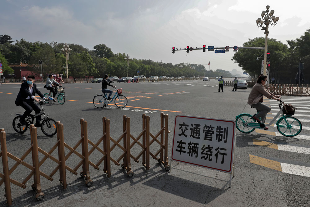 Masked cyclists ride past policemen blocked the cycling path leading to the Great Hall of the People and Tiananmen Square as delegates arrive to attend the opening session of China's National People's Congress in Beijing on Friday.