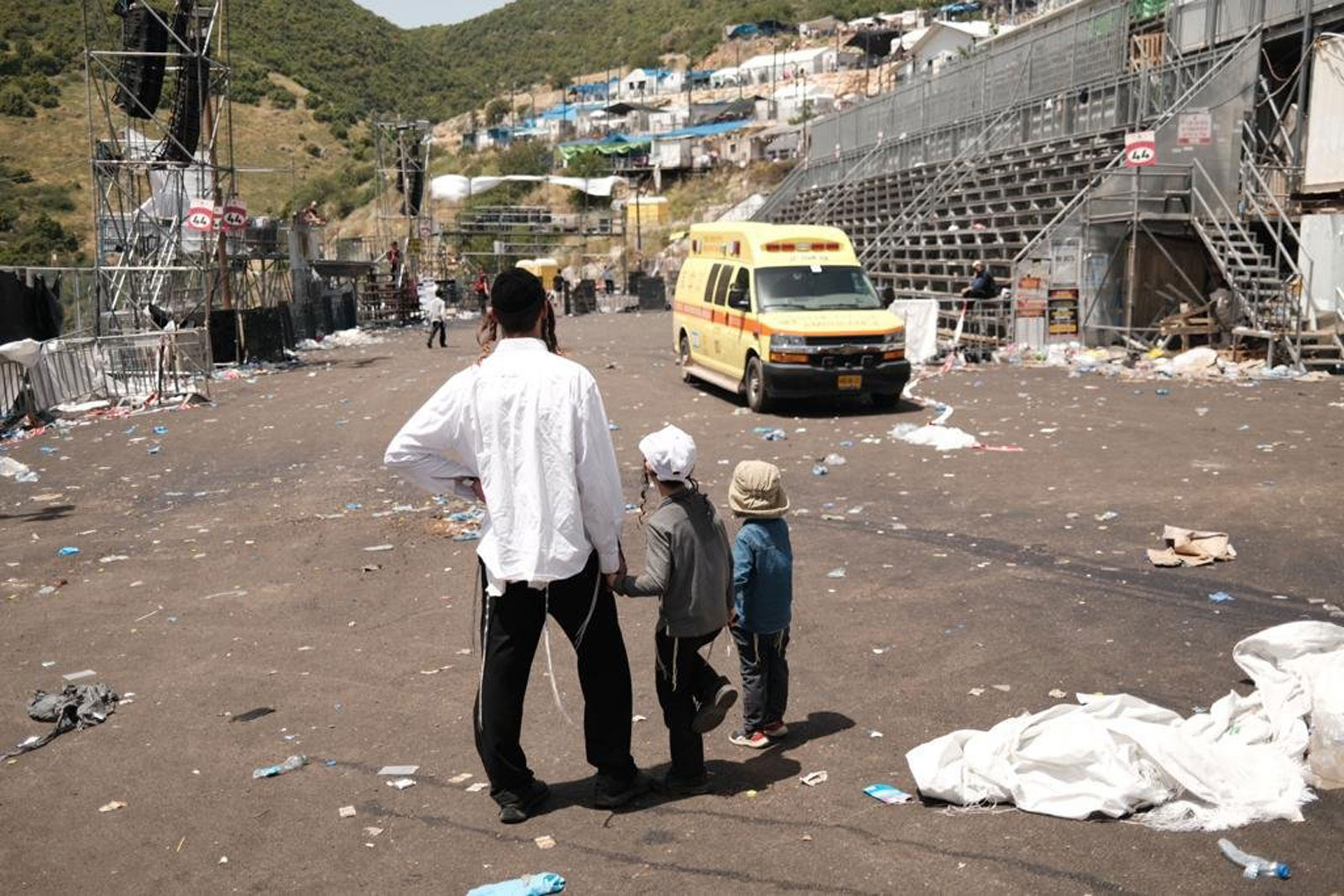 A family surveys the scene of the tragedy at Mount Meron on Friday.