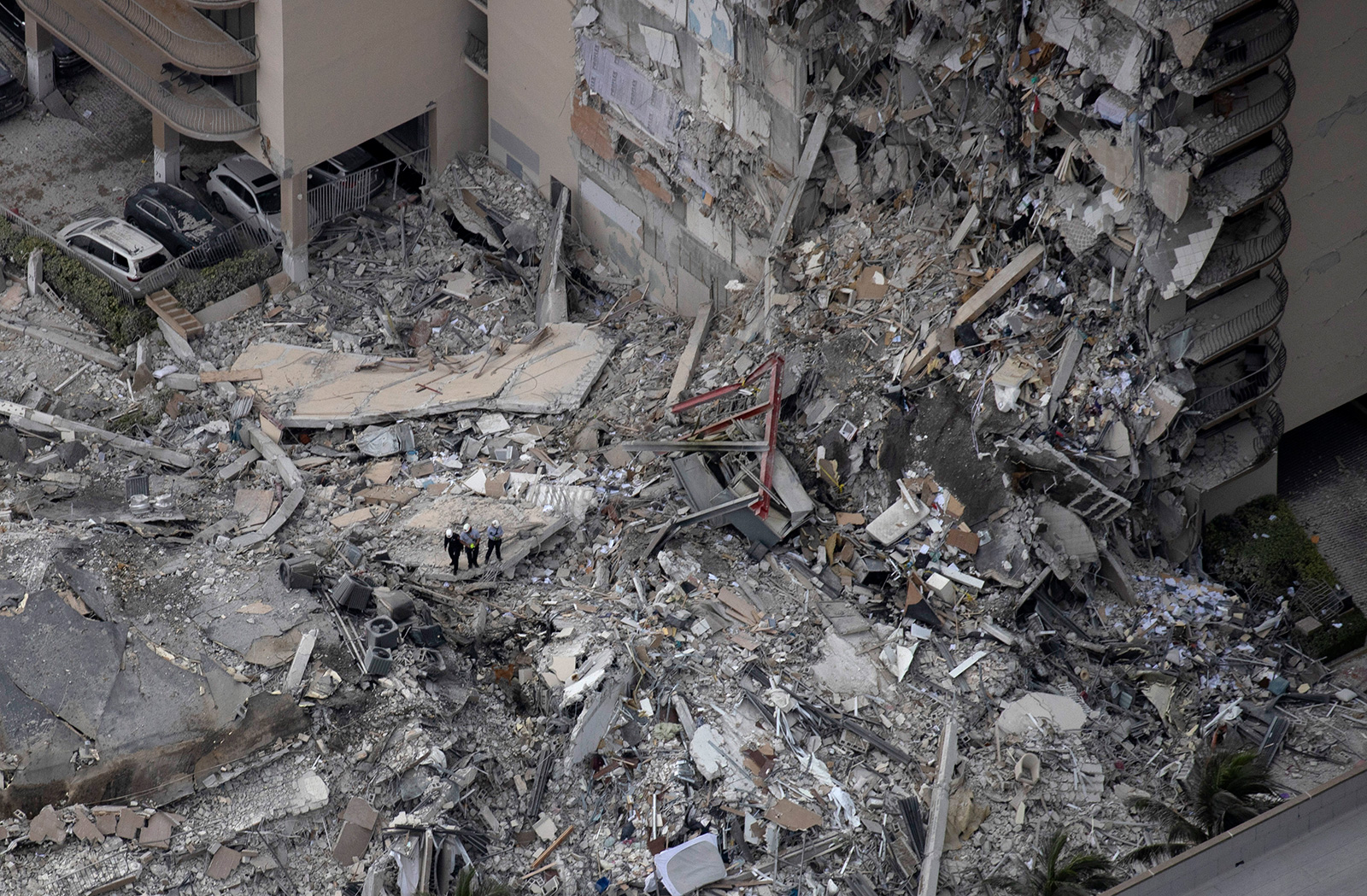 Search and rescue personnel with a K9 unit work in the rubble of a 12-story residential tower that partially collapsed on June 24, in Surfside, Florida.