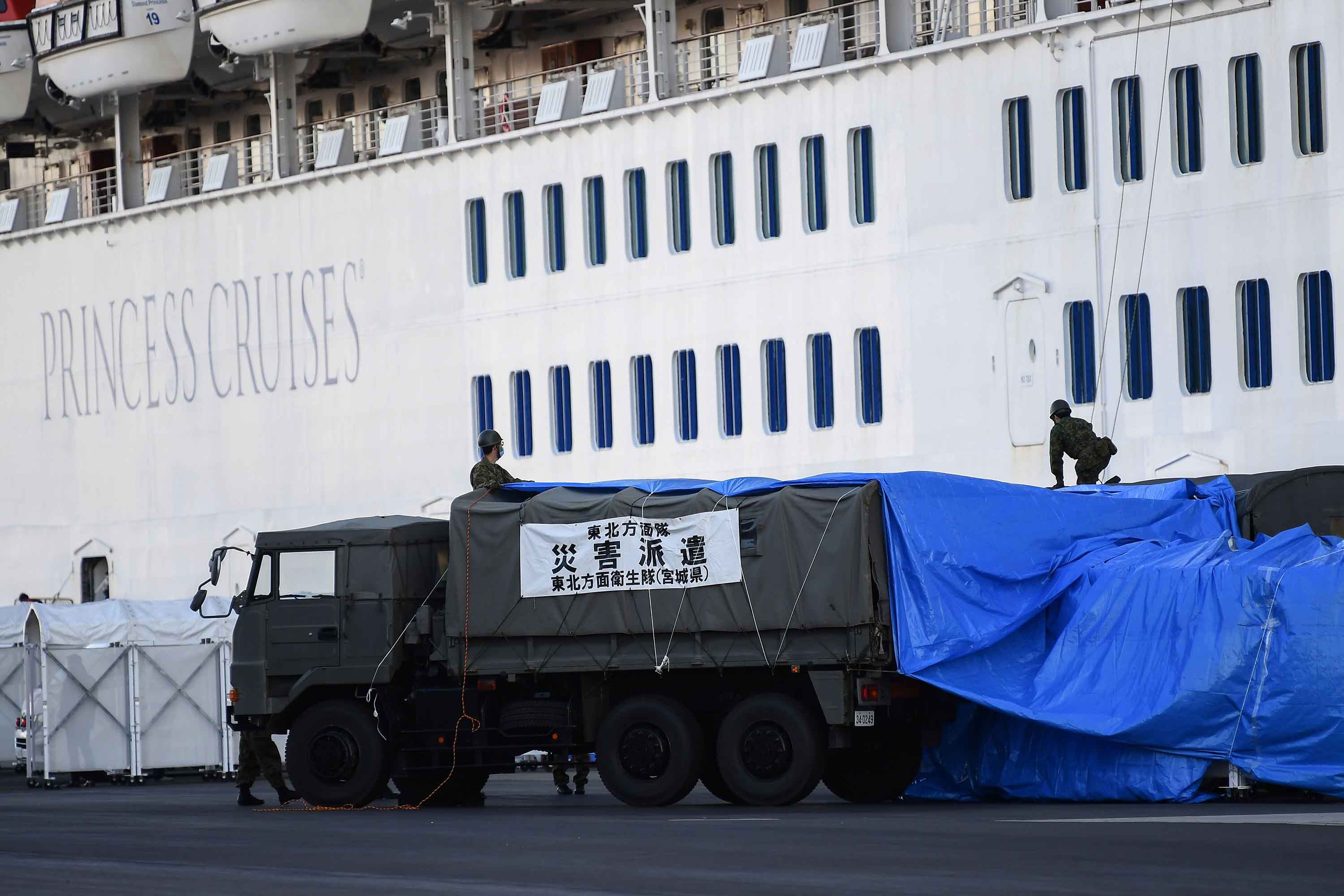 Japanese military personnel set up a covered walkway next to the Diamond Princess cruise ship on Monday in Yokohama, Japan.