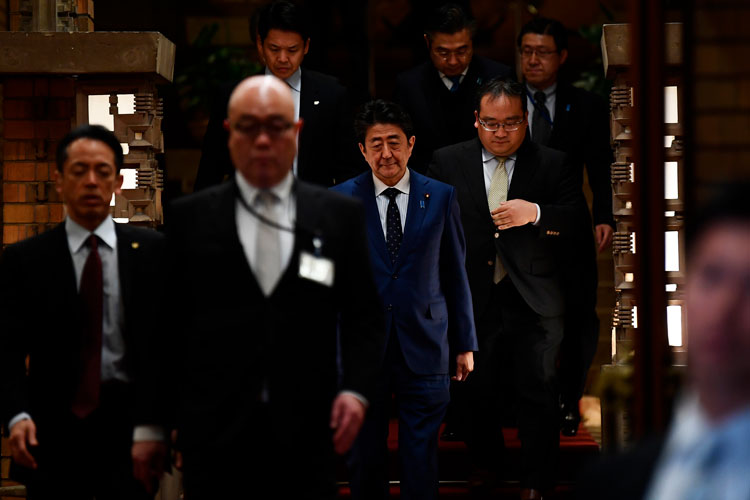 Japan's Prime Minister Shinzo Abe, center, arrives to speak to journalists in front of the prime minister's residence in Tokyo, Tuesday, March 24.