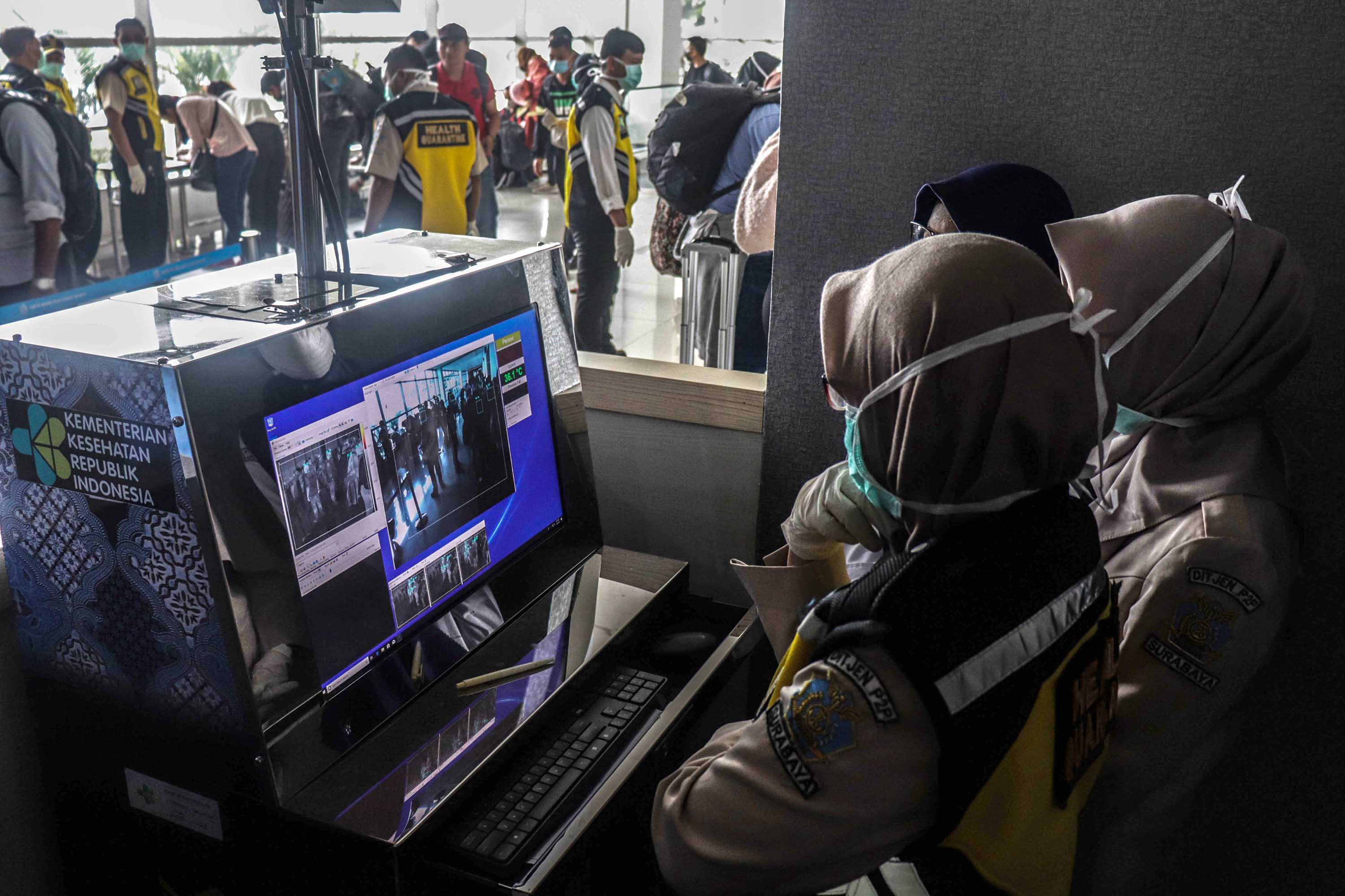 Health officers monitor a thermal scanner as passengers from Singapore, China and Hong Kong arrive at Juanda International Airport in Surabaya, East Java, Indonesia, on January 30.