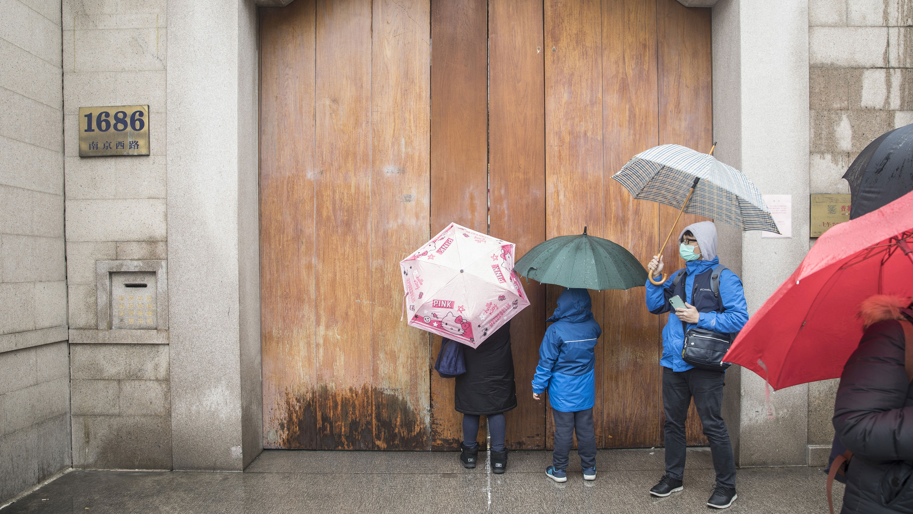 Visitors stand outside a closed temple in Shanghai, China, on Saturday, January 25.
