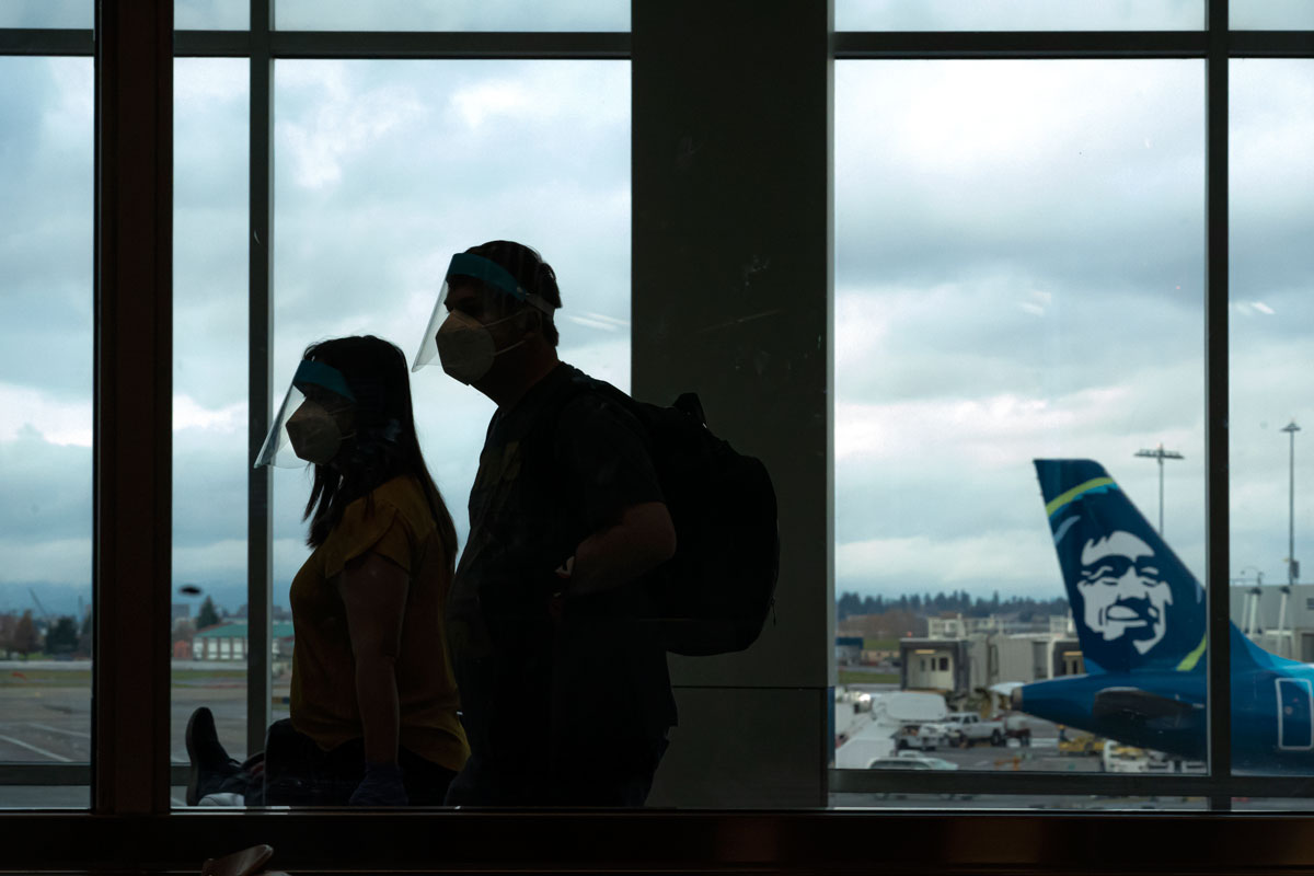 Travelers wearing face shields walk through Portland International Airport on November 25.