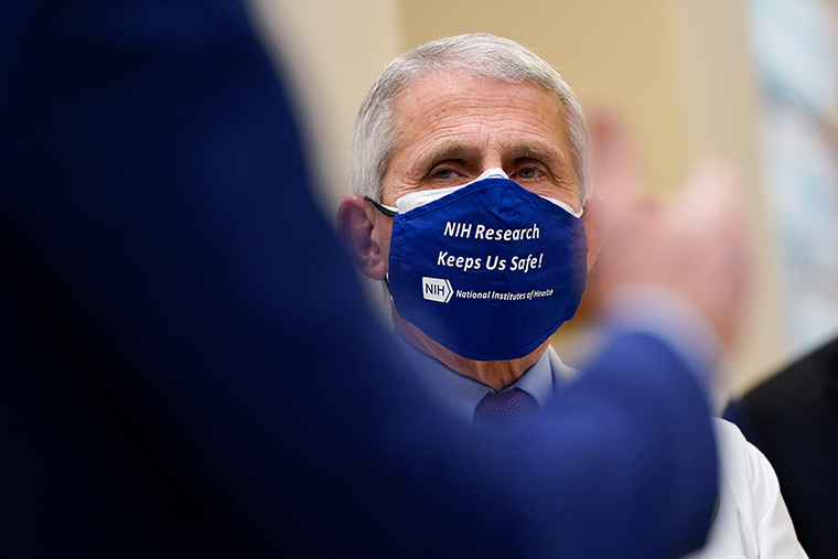 Dr. Anthony Fauci, director of the National Institute of Allergy and Infectious Diseases, listens as President Joe Biden speaks during a visit at the Viral Pathogenesis Laboratory at the National Institutes of Health (NIH), Thursday, Feb. 11, 2021, in Bethesda, Md.