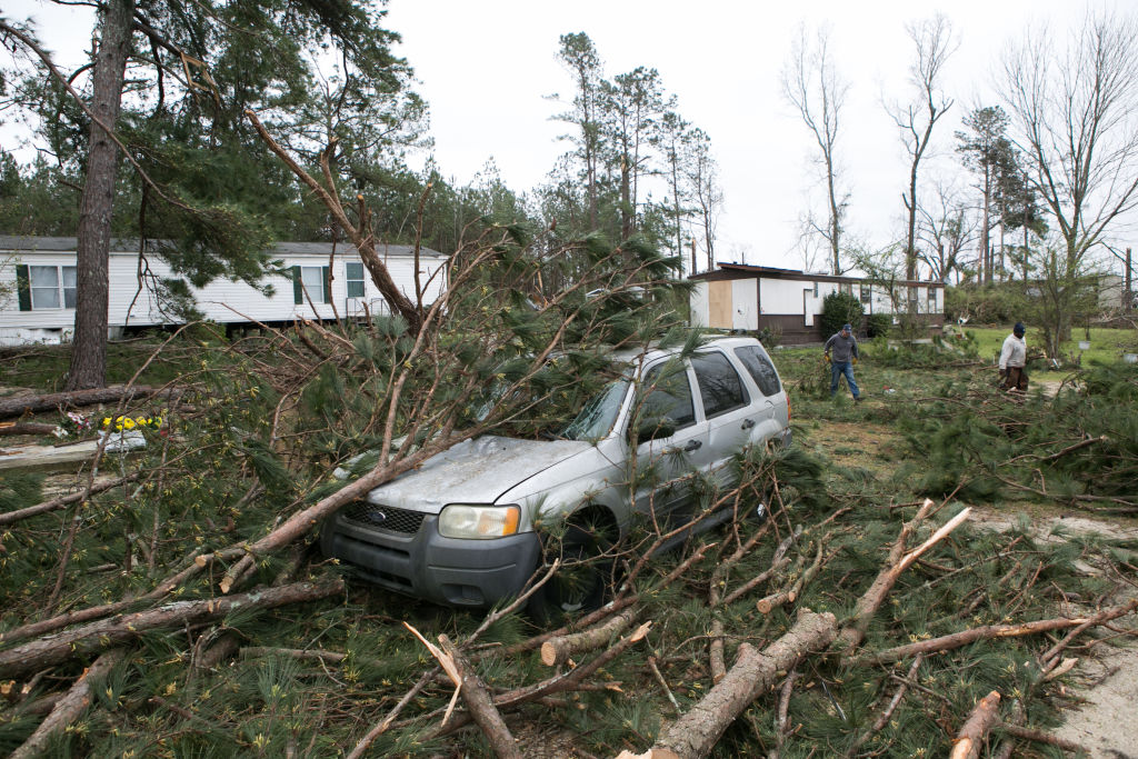 Volunteers and residents clean up trees and debris from a tornado at a home on March 4, 2019 in Beauregard, Alabama.