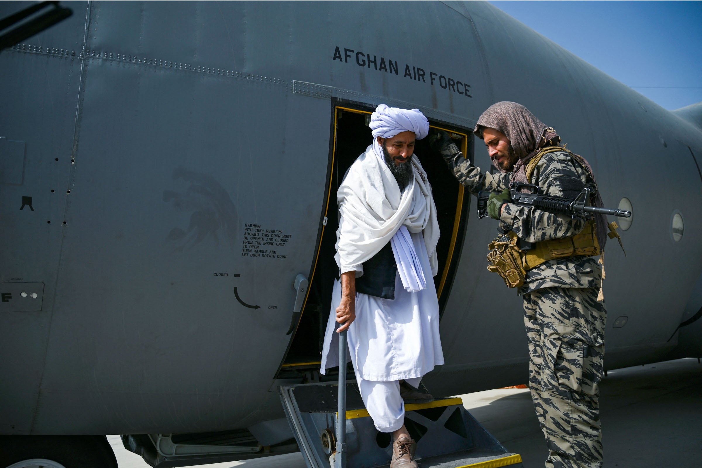 A member of the Taliban walks out of an Afghan Air Force aircraft at Kabul airport on Tuesday, August 31.