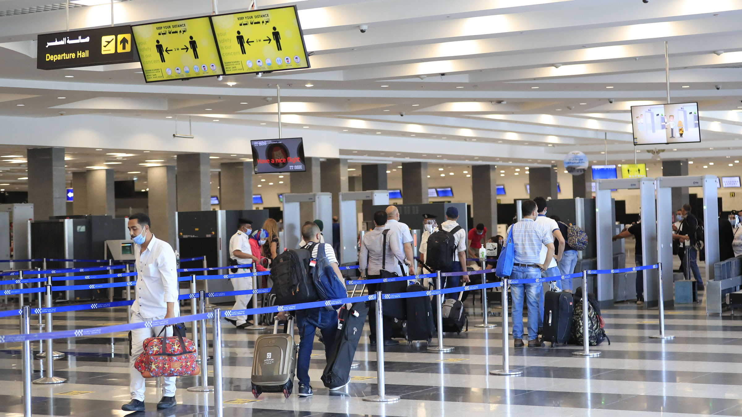 Travelers stand in line for a security check at the Sharm El Sheikh International Airport in June.