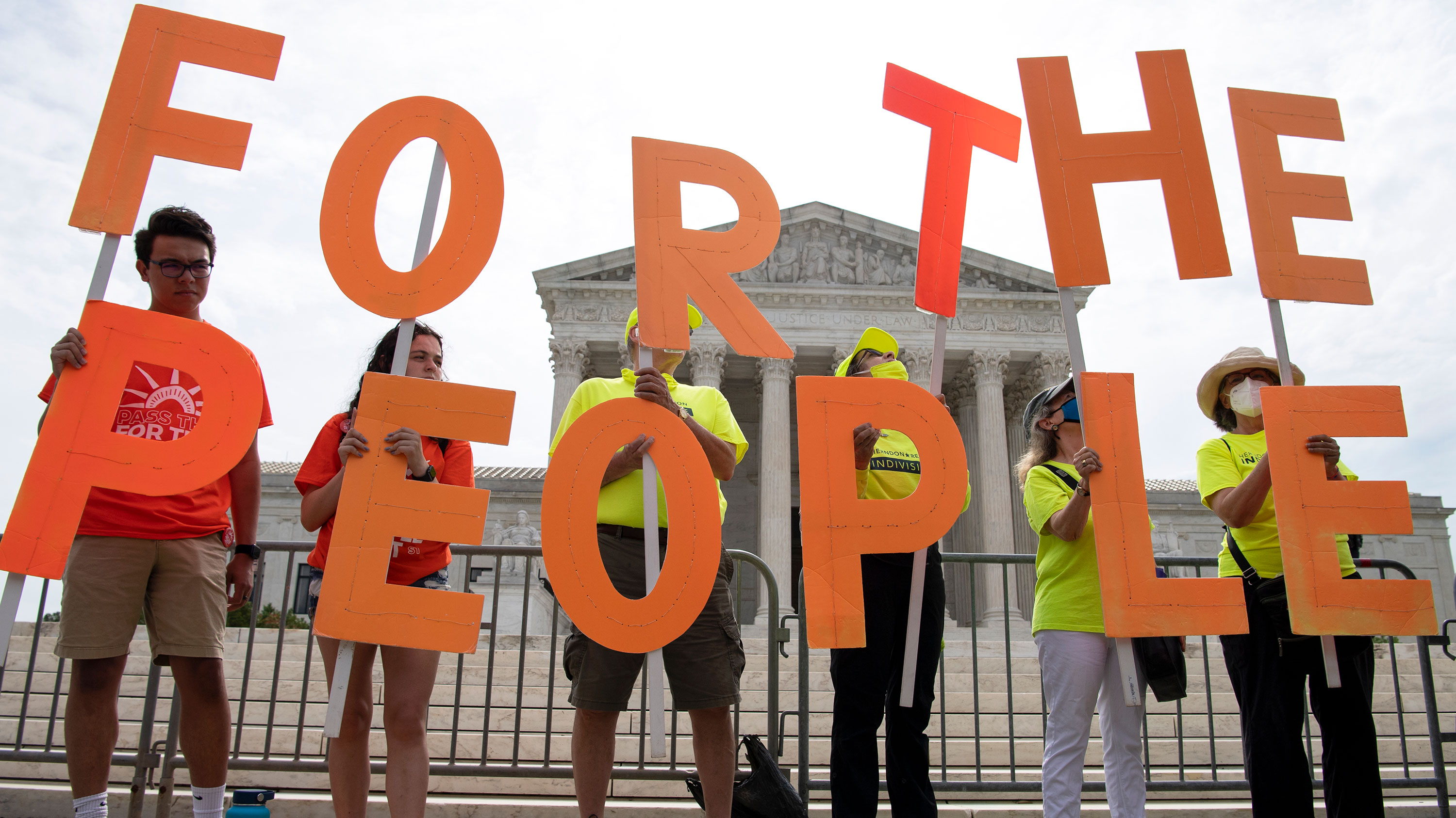 Demonstrators hold up signs as the Declaration for American Democracy coalition hosts a rally calling on the Senate to pass the For the People Act, outside the Supreme Court in Washington on Wednesday, June 9.