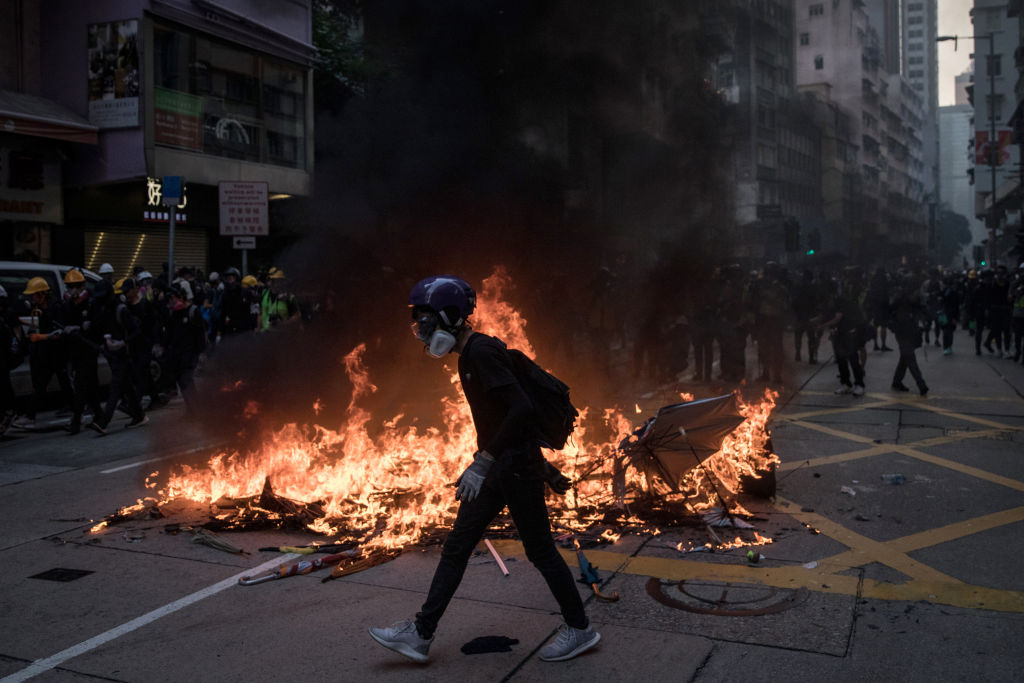 A pro-democracy protester walks in front of a burning barricade during clashes with police in Wan Chai on October 1, 2019 in Hong Kong