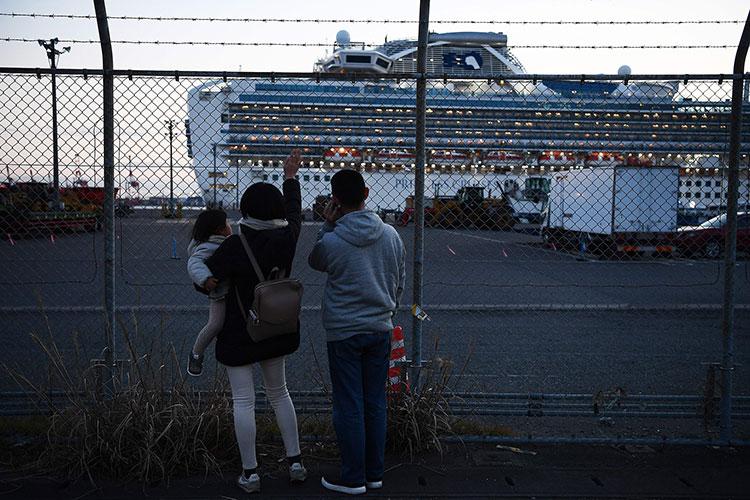 Relatives of passengers wave towards the Diamond Princess cruise ship in Yokohama on February 11, 2020.