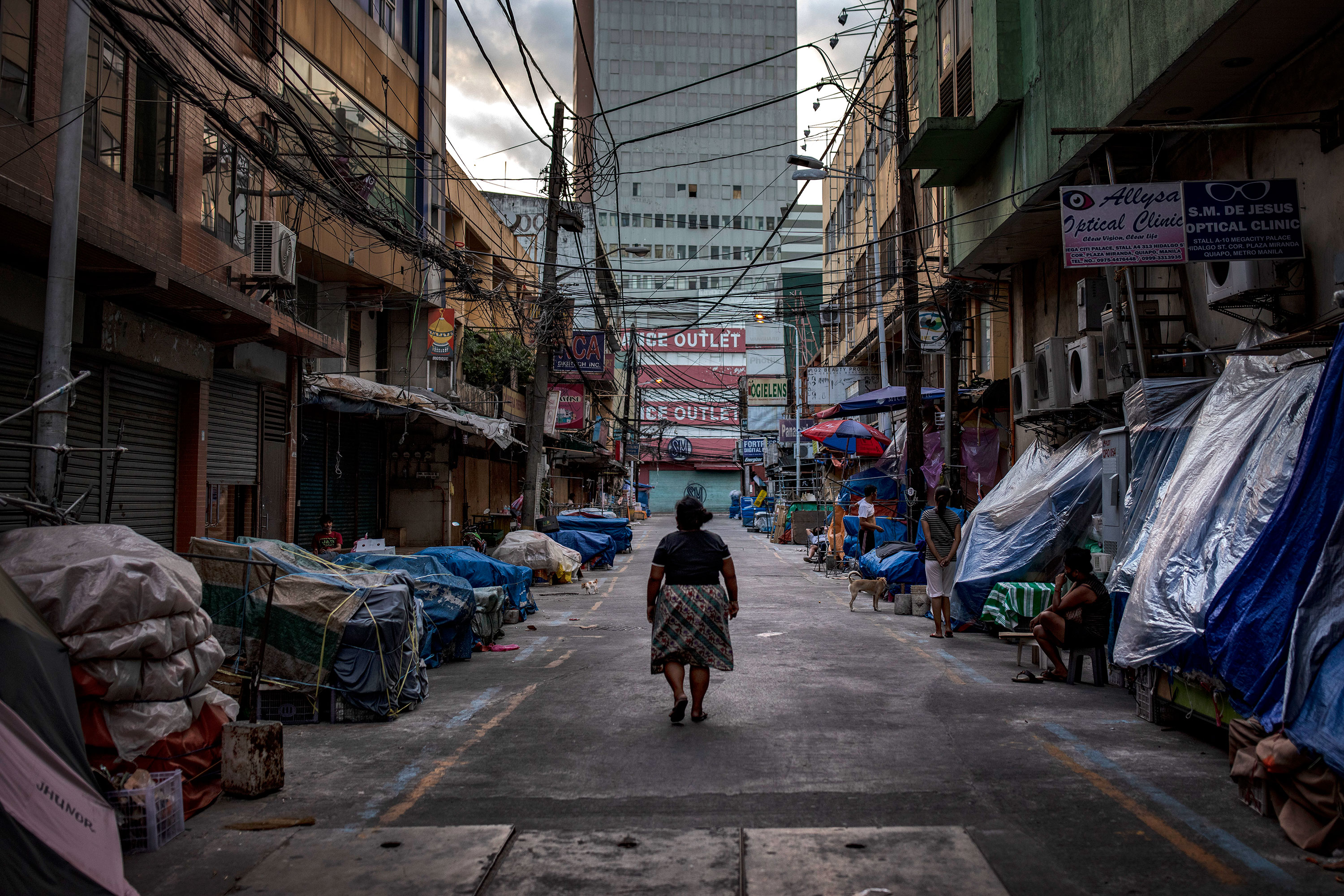 A woman walks past closed stalls at the Quiapo shopping district on March 30 in Manila, Philippines.