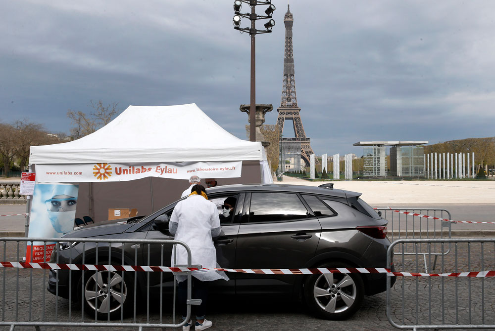 A medical biologist wearing a protective mask administers a nasal swab to a patient at a drive-through testing site for the coronavirus at the Champs de Mars next to the Eiffel tower on April 6, in Paris.