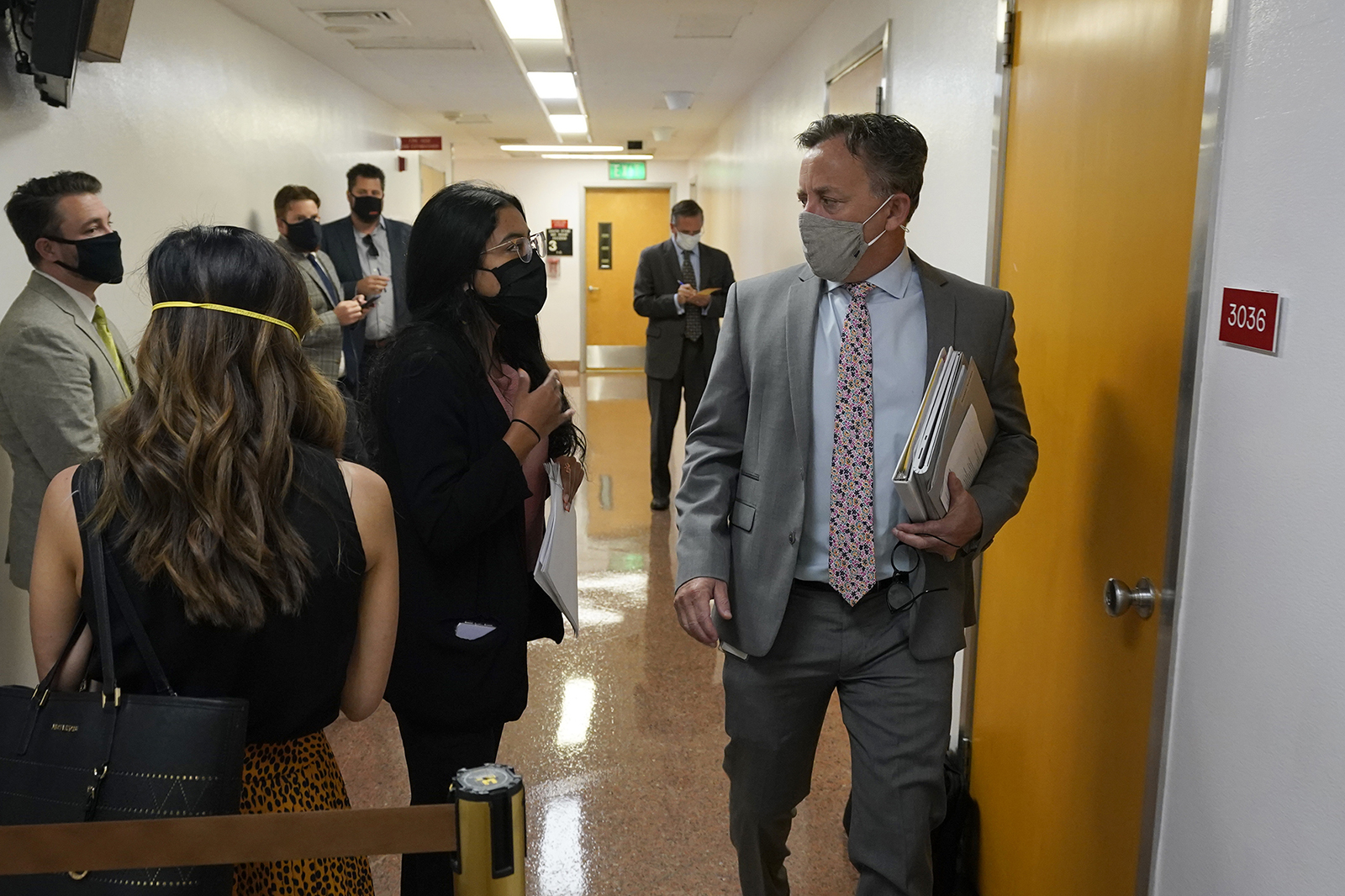 In this Sept. 2, 2021 file photo Democratic State Sen. Josh Newman passes lobbyists and activists as he walks to the Senate chambers at the Capitol in Sacramento.