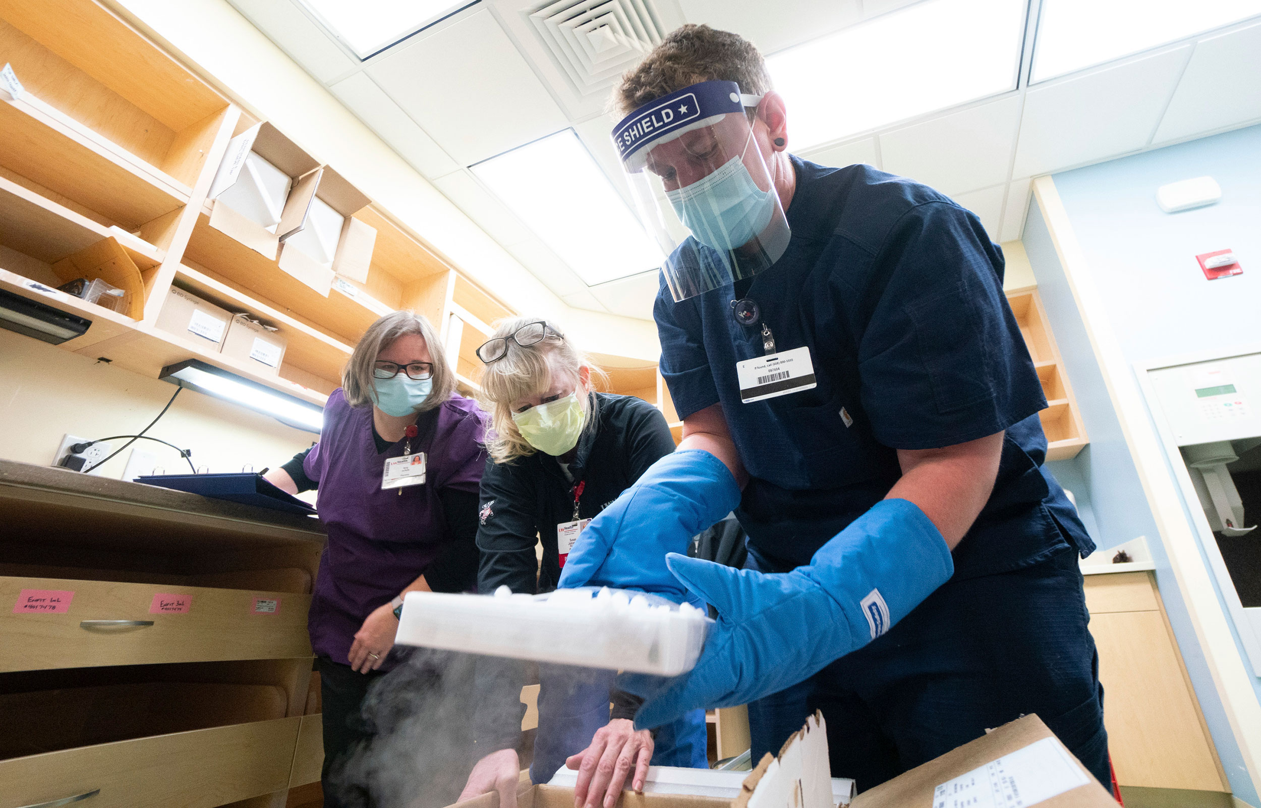 From left, UW Health pharmacy techs Amy Schultz, Susan Johnson and Nikolas Gardner unpack the first shipment of the Pfizer vaccine in Madison, Wisconsin, on Monday.