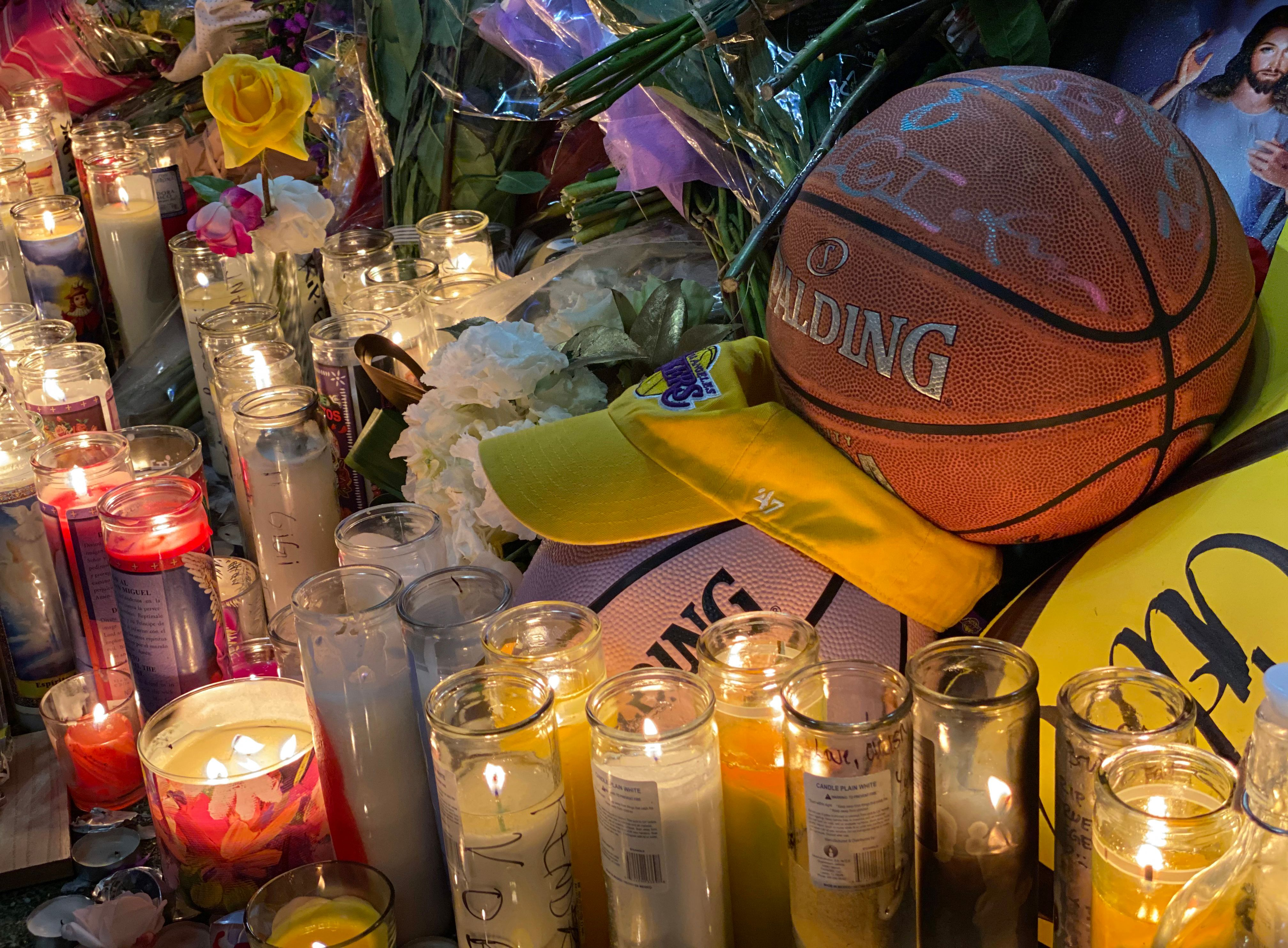 Candles are displayed at a makeshift memorial in front of a mural in downtown Los Angeles.