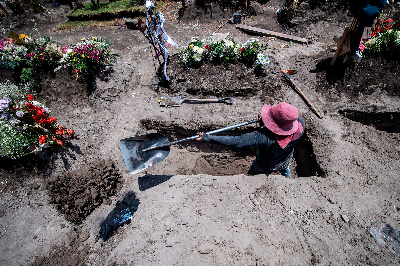 A gravedigger digs a grave during a funeral at the San Miguel Xico cemetery in Mexico on August 5.