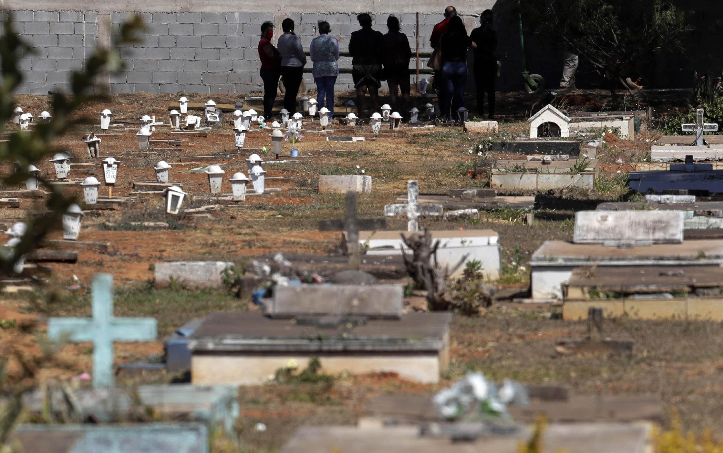 People attend the burial of Jose Mario de Souza Veiga, 83, whose family said died of COVID-19, at the Campo da Esperanca cemetery in Brasilia, Brazil, on Tuesday, July 21.
