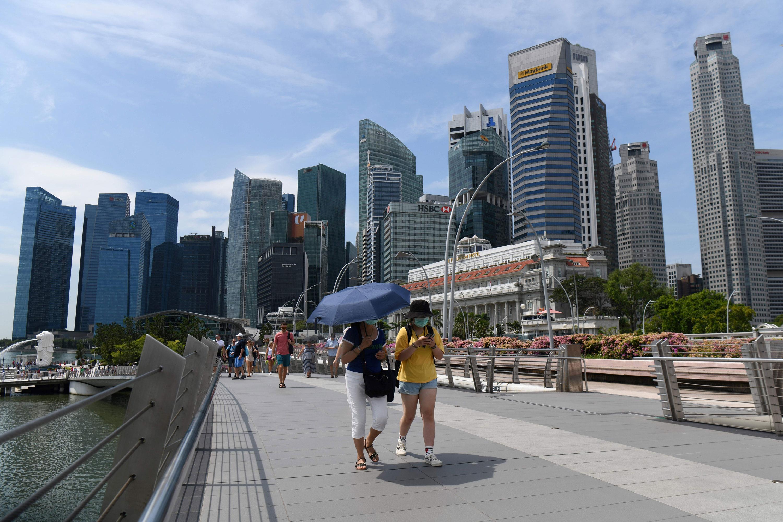 People wearing protective face masks walk along Singapore's Jubilee Bridge on Monday.
