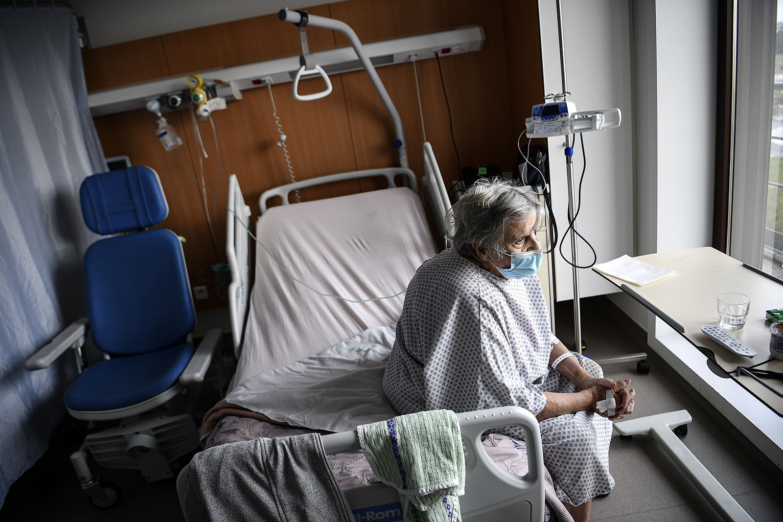 A patient infected with Covid-19 sits on her bed in the infectious diseases unit of the Gonesse hospital in Gonesse, north of Paris, on October 22.