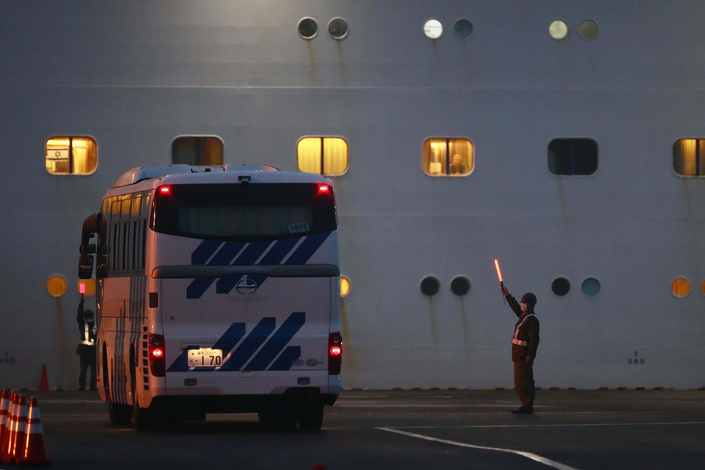 A bus arrives next to the Diamond Princess cruise ship in Yokohama port on Sunday.