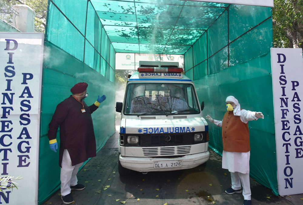 An ambulance passes through a disinfecting tunnel at the Hindu Rao Hospital in New Dehli on April 12.