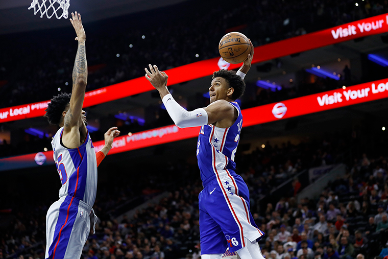 Philadelphia 76ers' Matisse Thybulle, right, goes up for a dunk against Detroit Pistons' Christian Wood during the second half of an NBA basketball game, Wednesday, March 11, in Philadelphia.