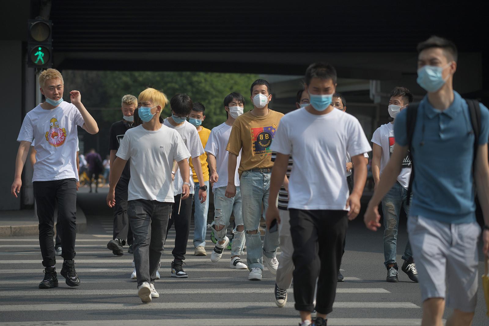 People wear masks as they cross a road in Beijing on June 28.