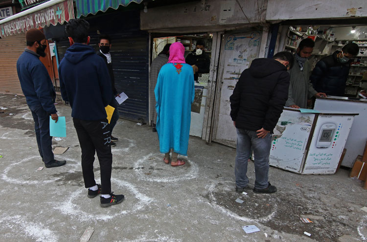 People maintain social distancing, due to the coronavirus pandemic as they wait for their turn to collect medicines from a pharmacy in Srinagar, Kashmir, India on March 26.