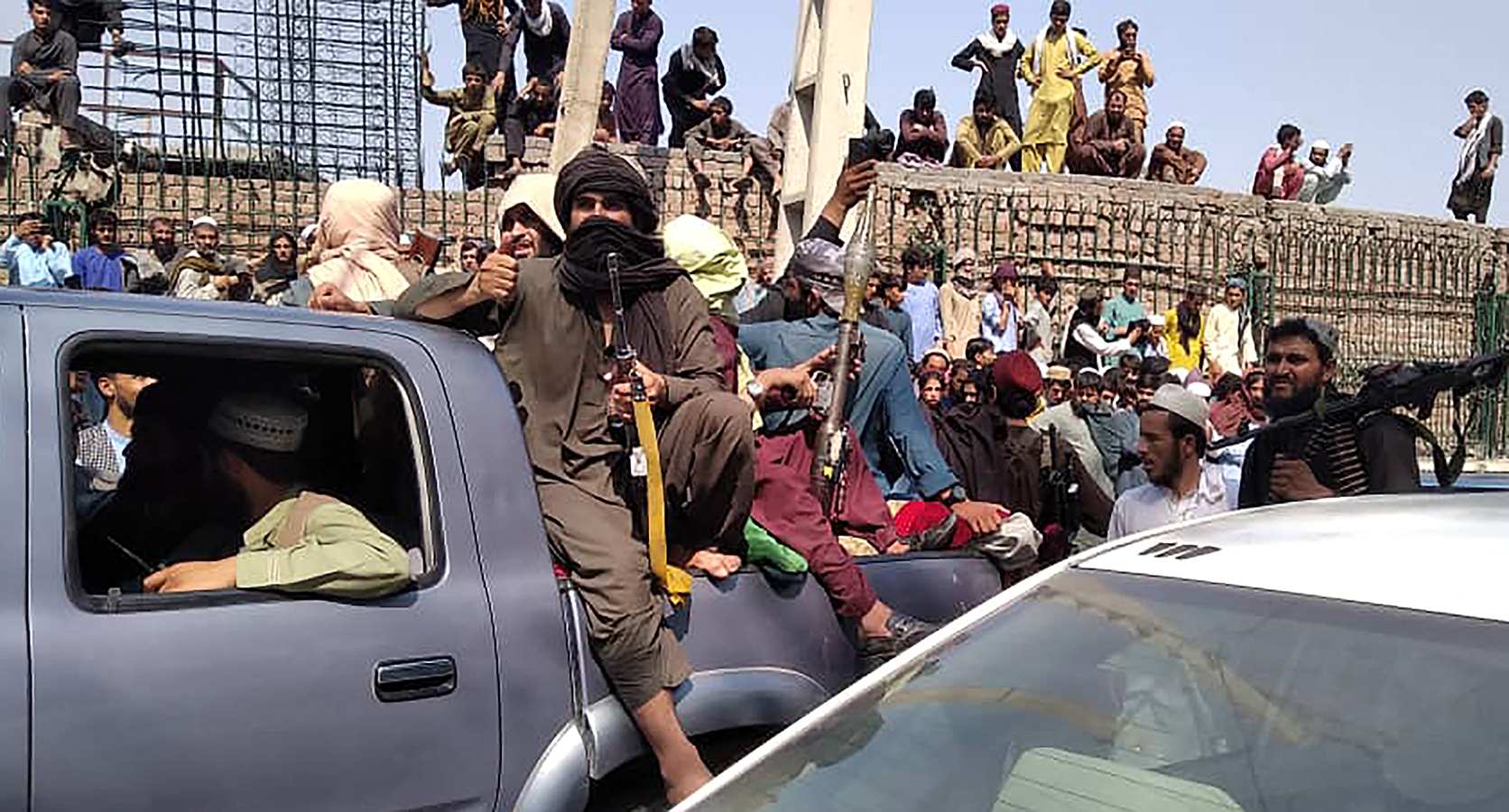 Taliban fighters sit on a vehicle along the street in Jalalabad province, Afghanistan on August 15.