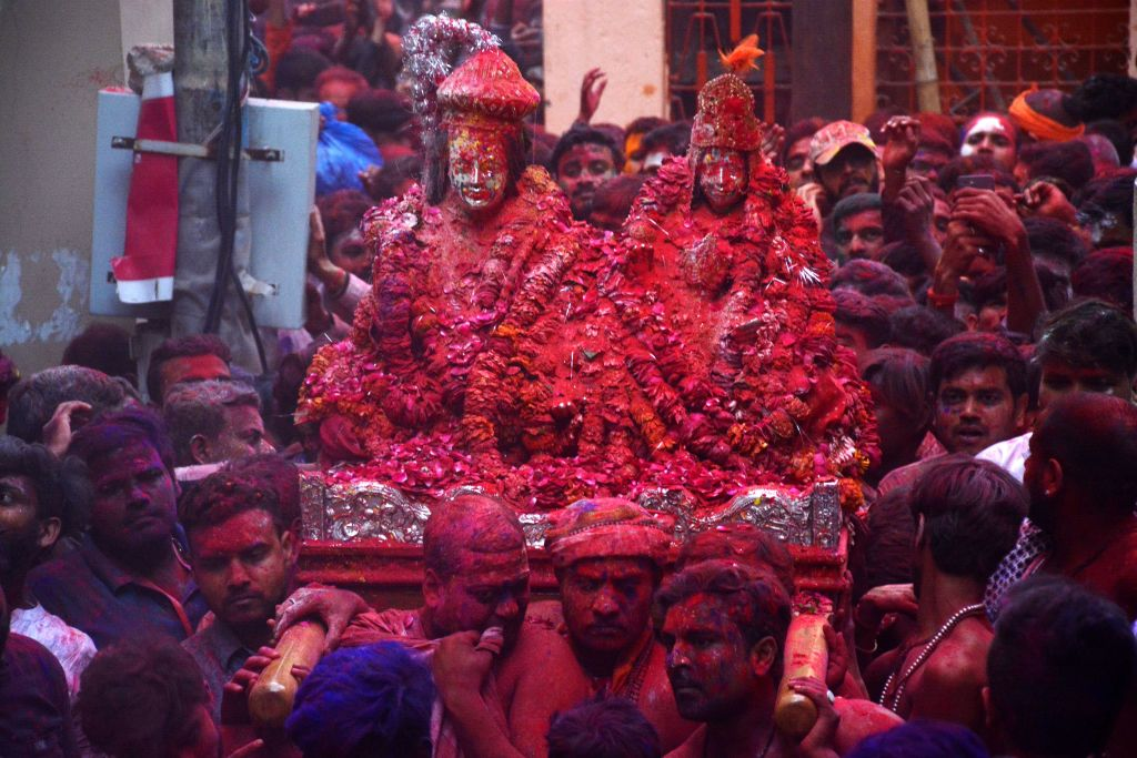 Hindu devotees smeared in colored powder carry the images of Lord Shiva, left, and Goddess Parvati from the Kashi Vishwanath temple during Holi, the spring festival of colours, in Varanasi on March 5.