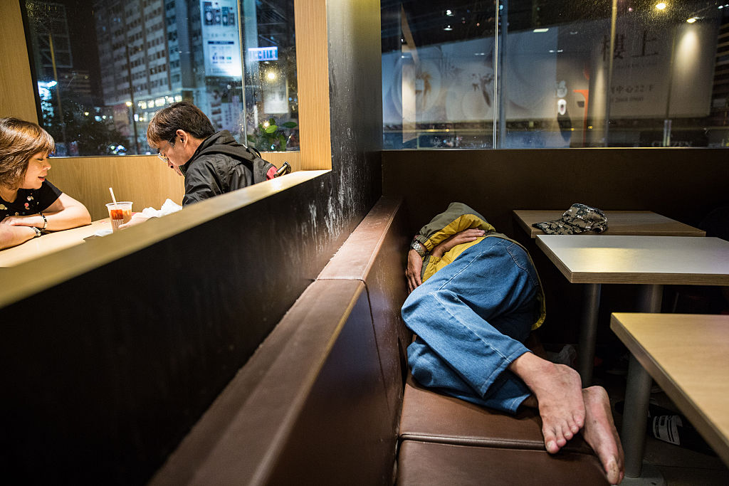 A couple sit for a meal as a man sleeps on a bench at a McDonalds outlet in the Kowloon district of Hong Kong on April 8, 2016.