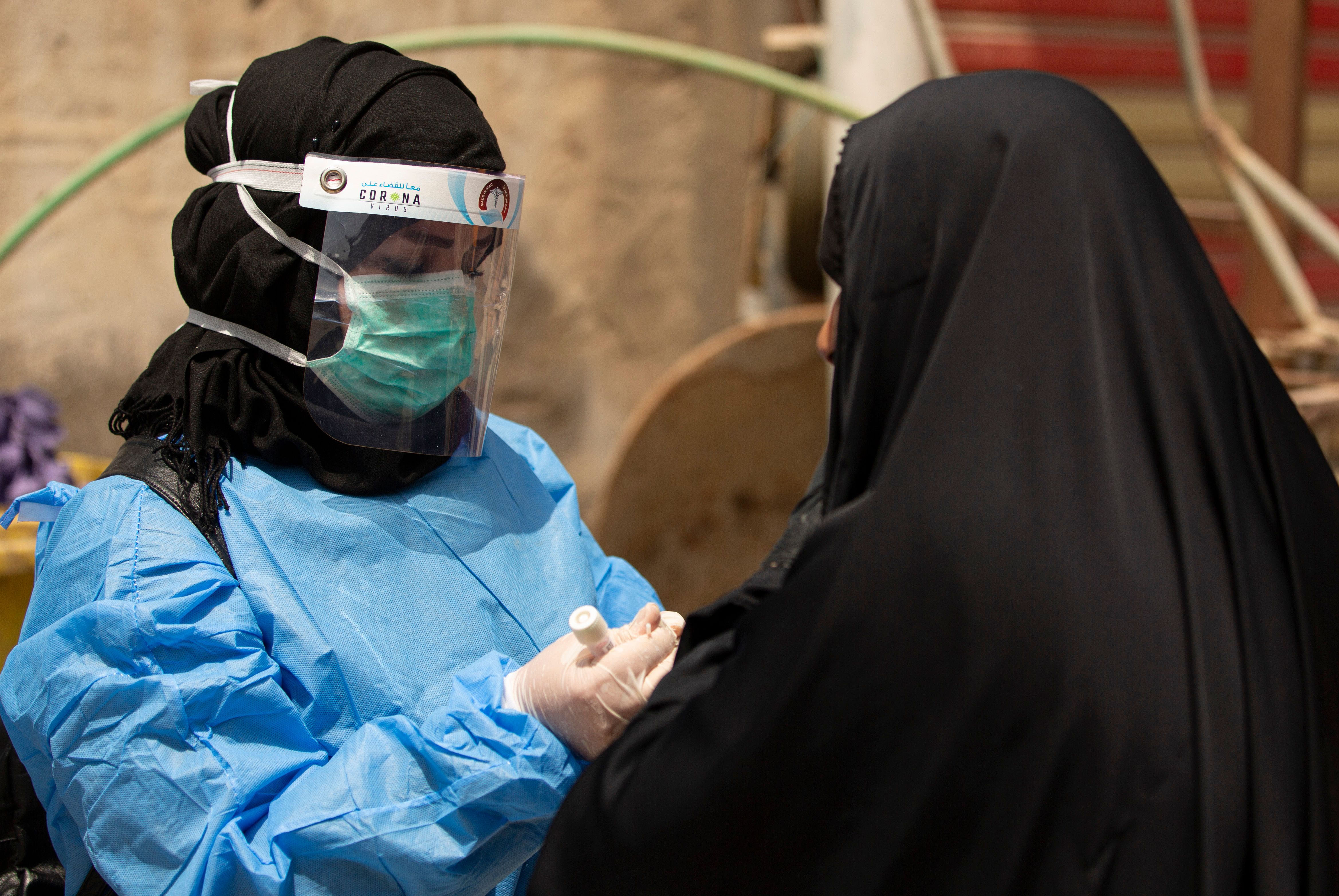 A medical worker prepares to take a swab from a person being tested for Covid-19 in Basra, Iraq, on June 2.