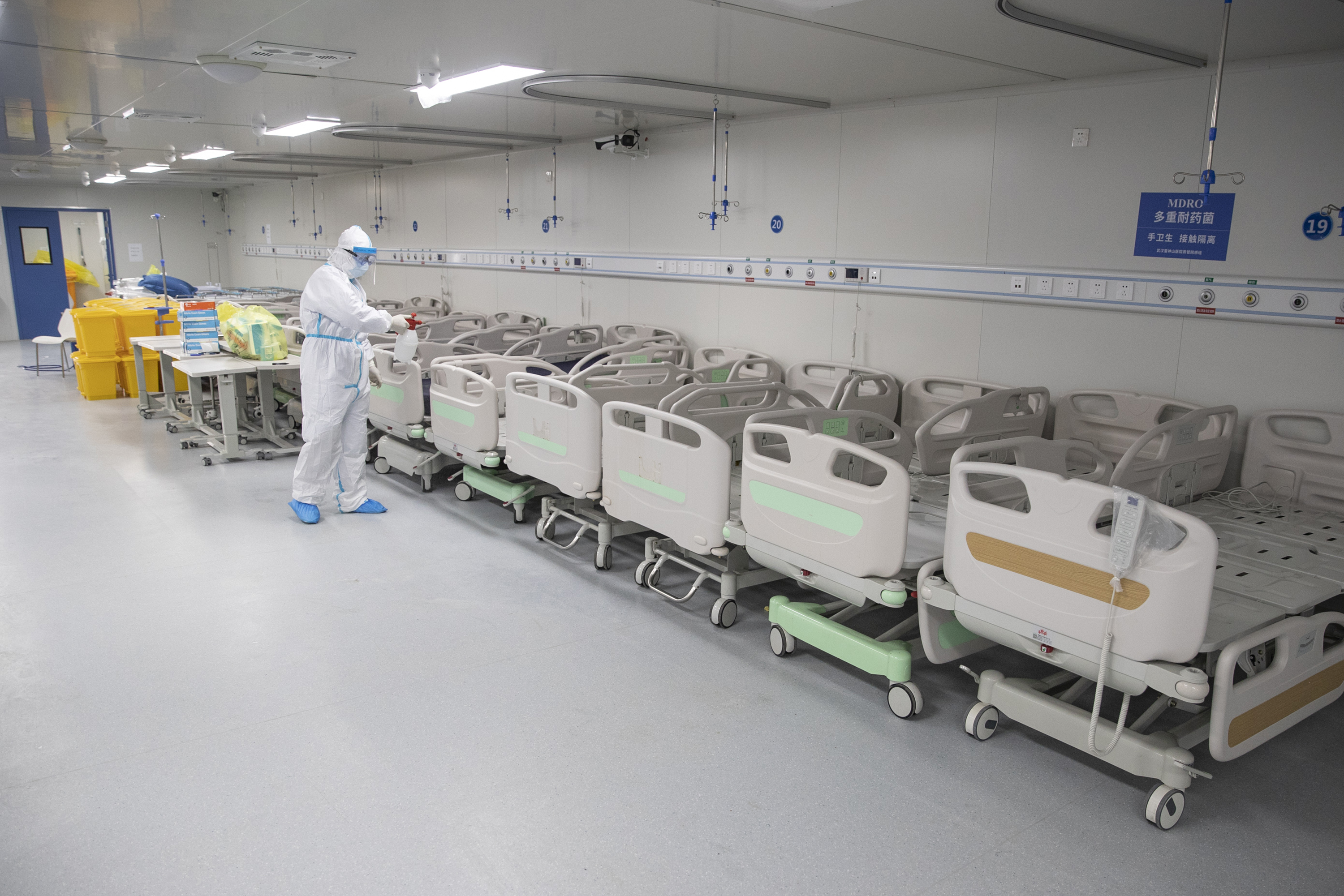 A staff member sprays disinfectant on empty beds after all patients left Leishenshan Hospital in Wuhan in China's central Hubei province. The hospital, built in less than two weeks to handle a large number of Covid-19 patients closed on April 14.