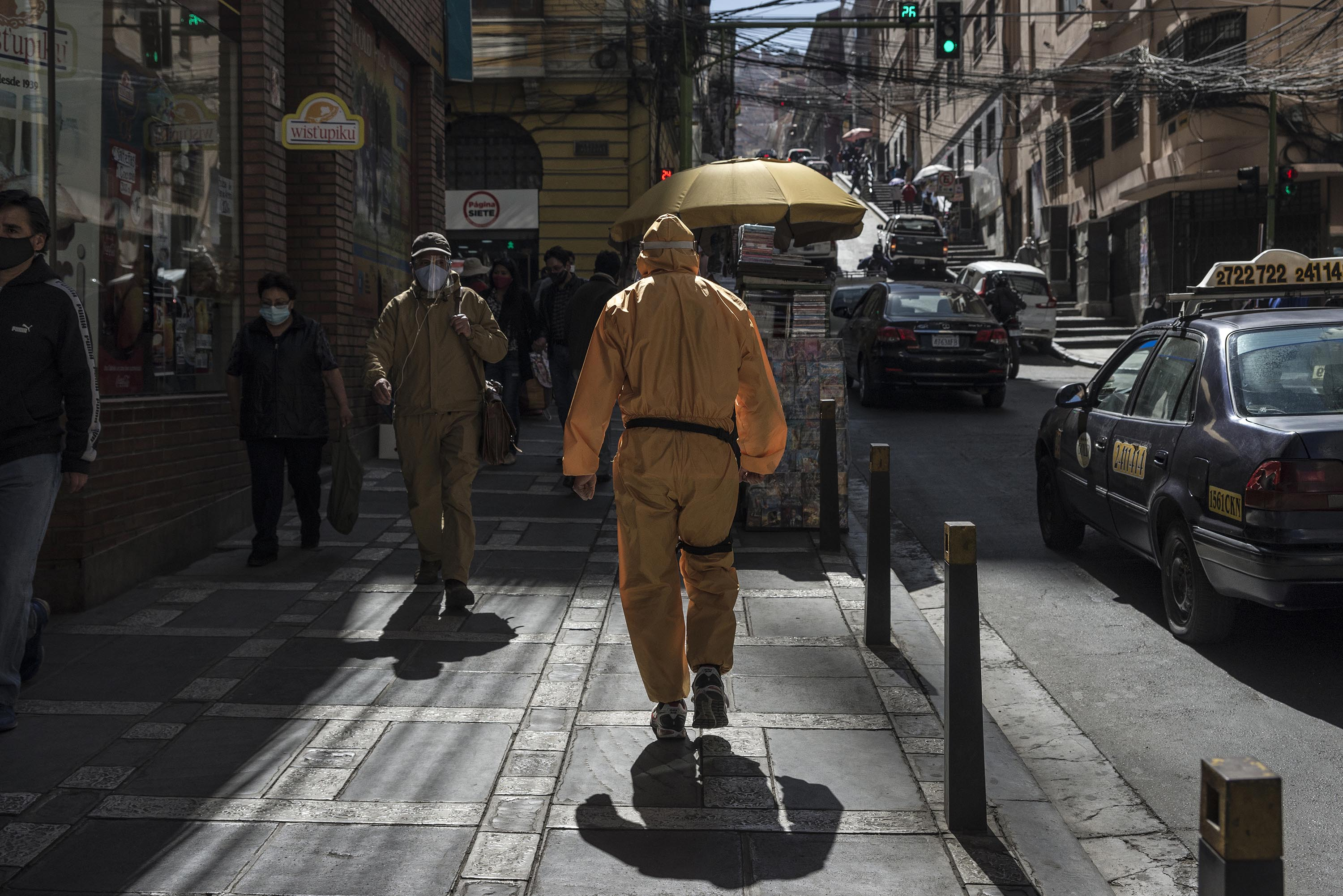A man wearing a protective mask and suit walks down a street in La Paz, Bolivia, on Monday, July 20.