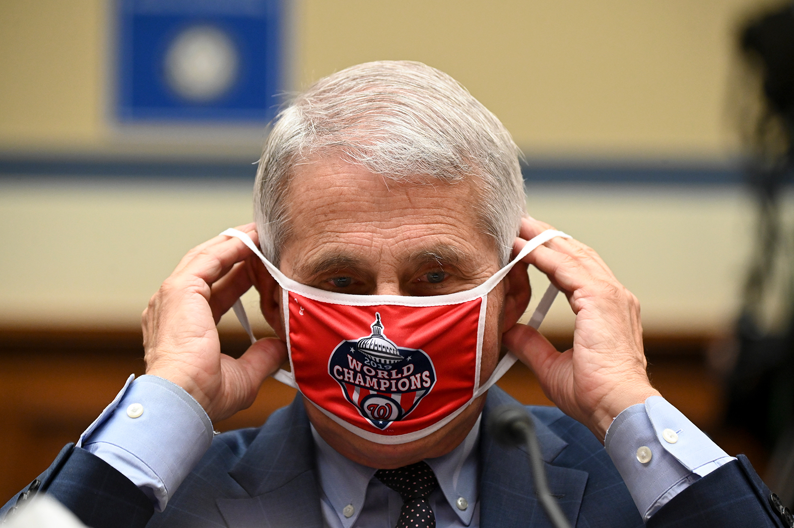 Anthony Fauci, director of the National Institute of Allergy and Infectious Diseases, removes his Washington Nationals protective mask during a House Select Subcommittee on the Coronavirus Crisis hearing on July 31 in Washington.