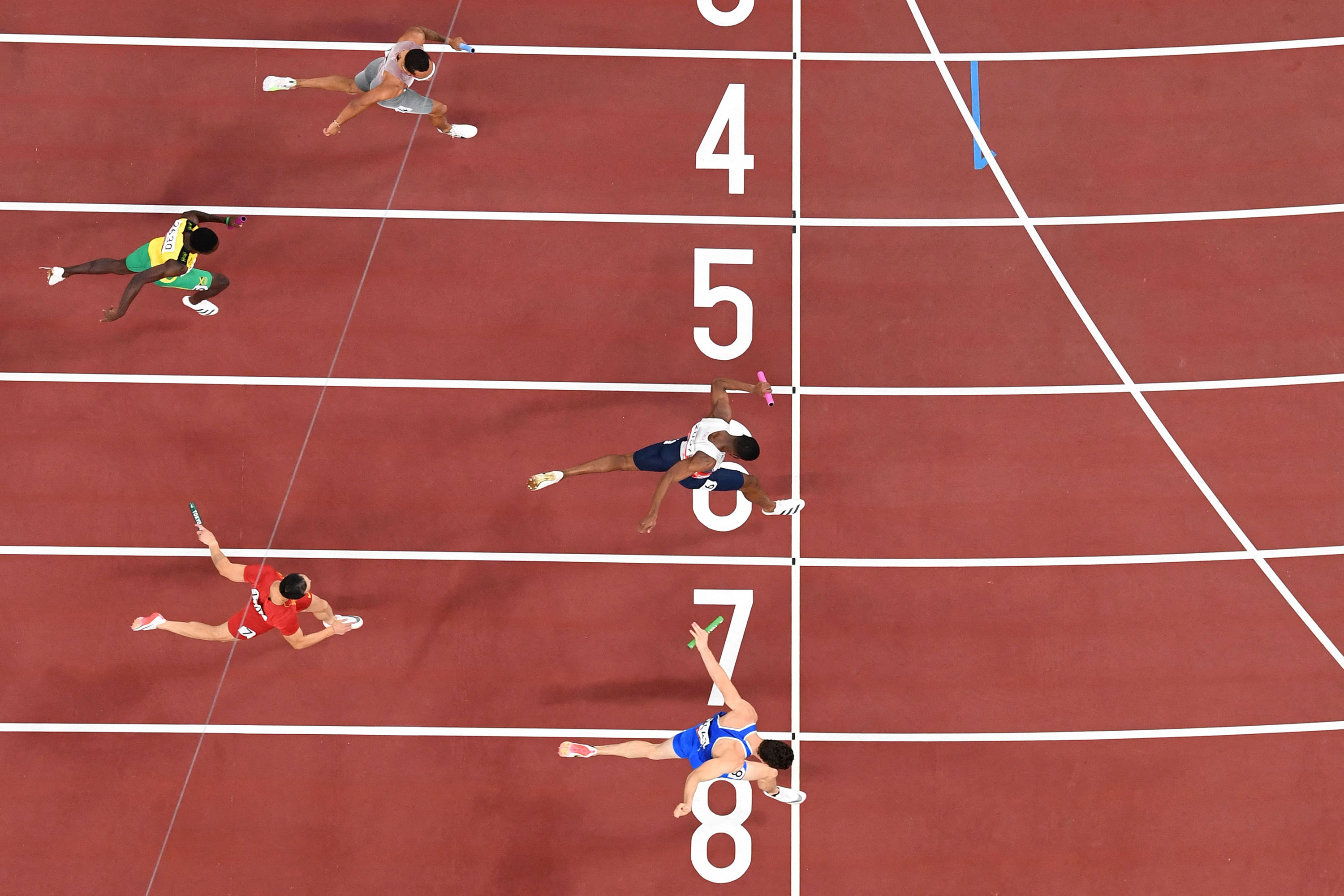 Italy's Filippo Tortu, bottom, finishes first in the 4x100 meter relay final on Friday.