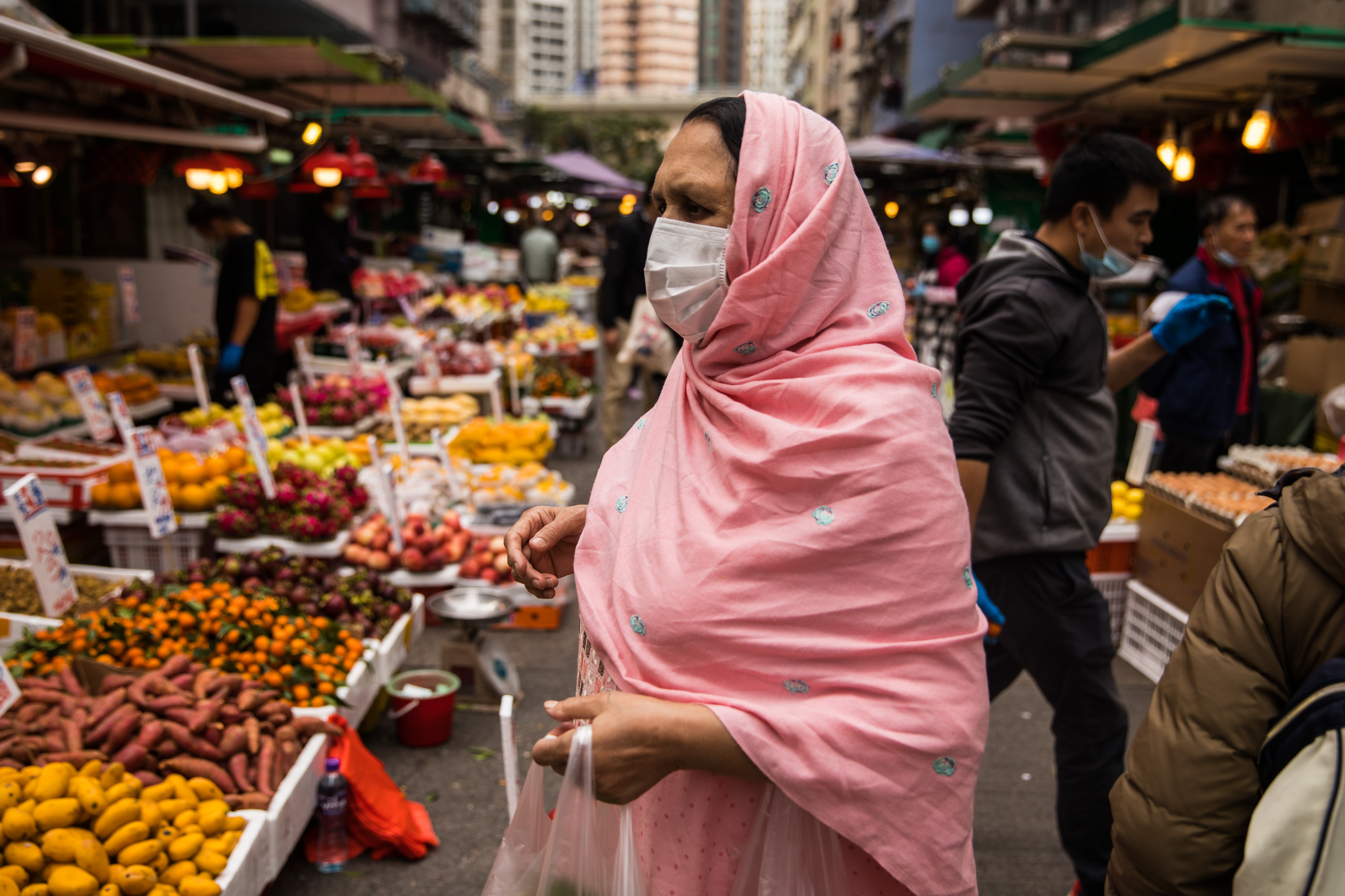 A woman wearing a protective face mask shops at a fresh food market in Hong Kong on Sunday.