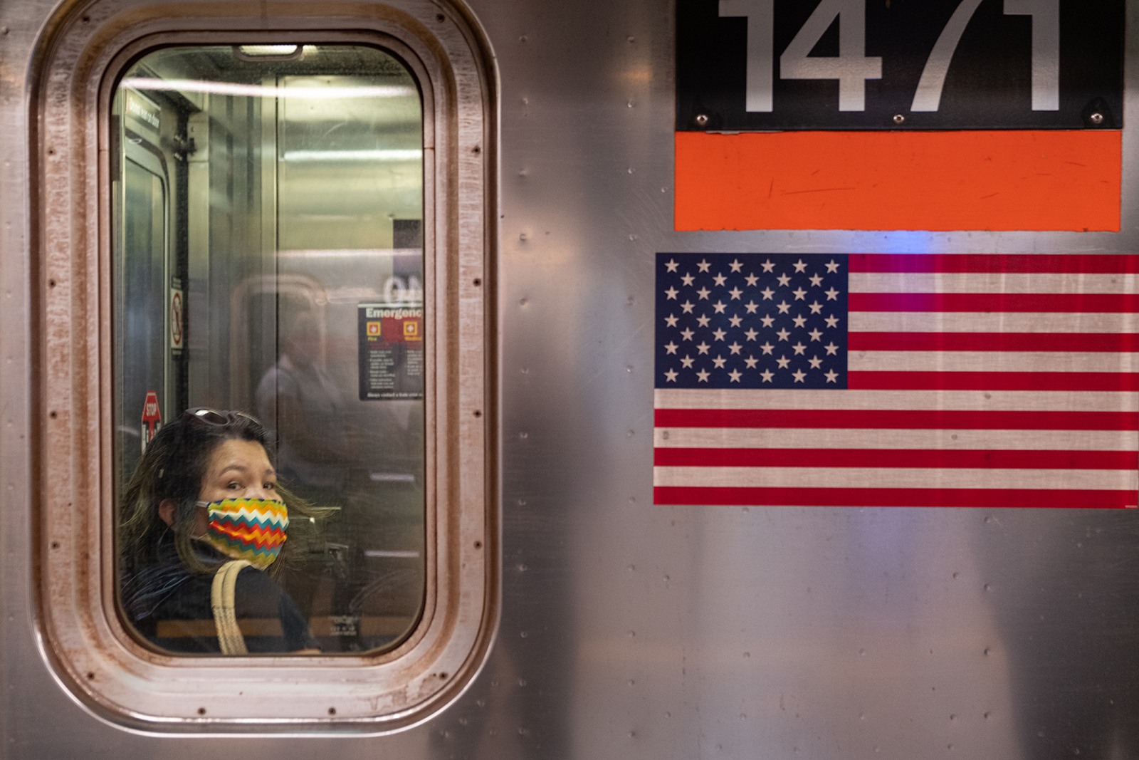 A woman wearing a mask rides the subway during rush hour on June 8, in New York City.