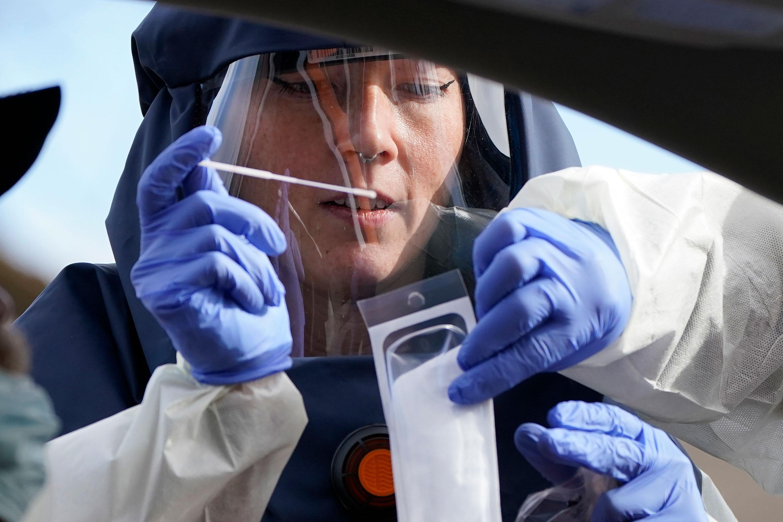 A county health department public health nurse performs a coronavirus test on November 13 in Salt Lake City, Utah.