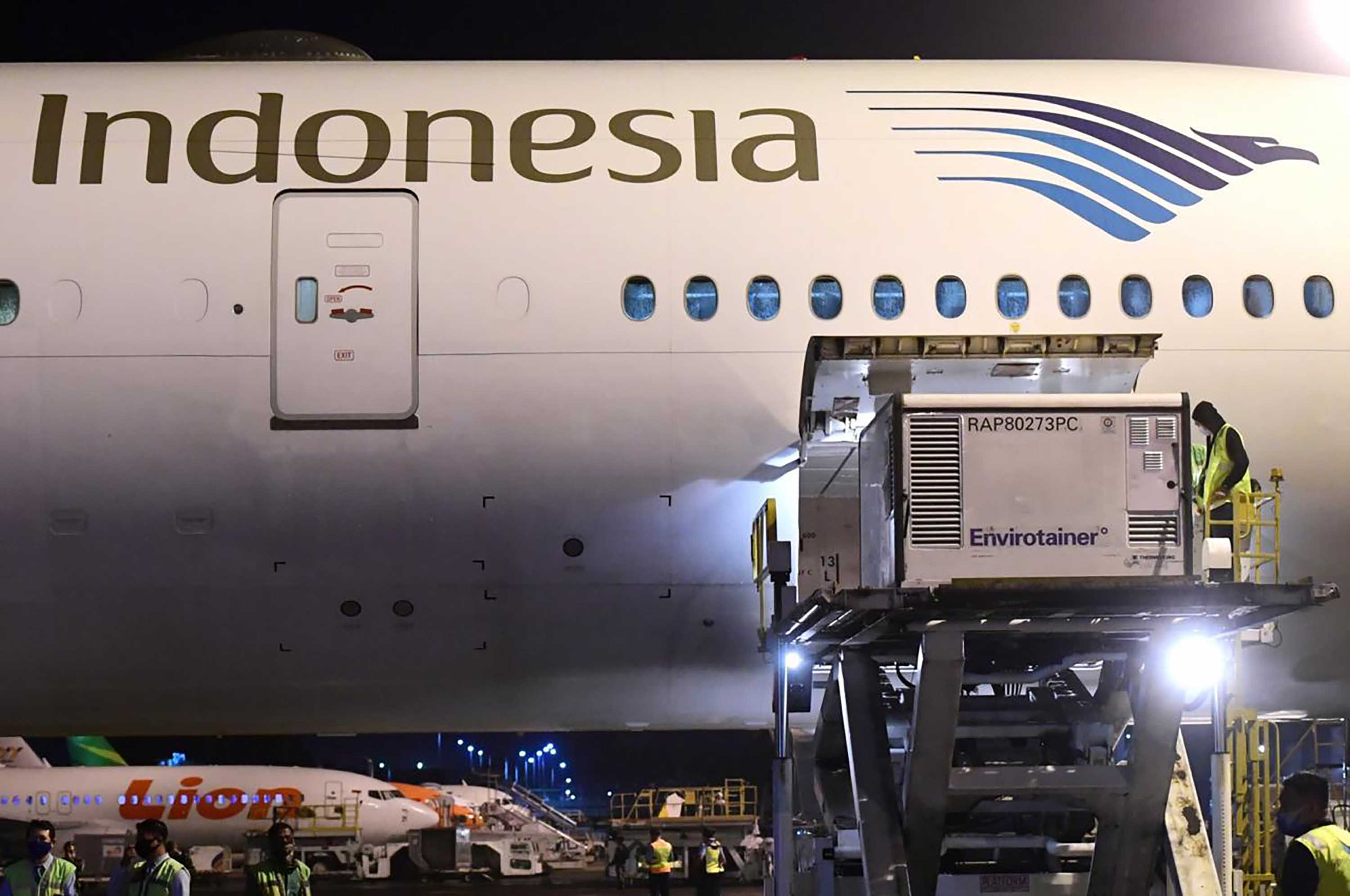 Workers unload a shipment of the Covid-19 vaccine made by Sinovac, upon its arrival from Beijing at the Jakarta International Airport in Indonesia on December 6.