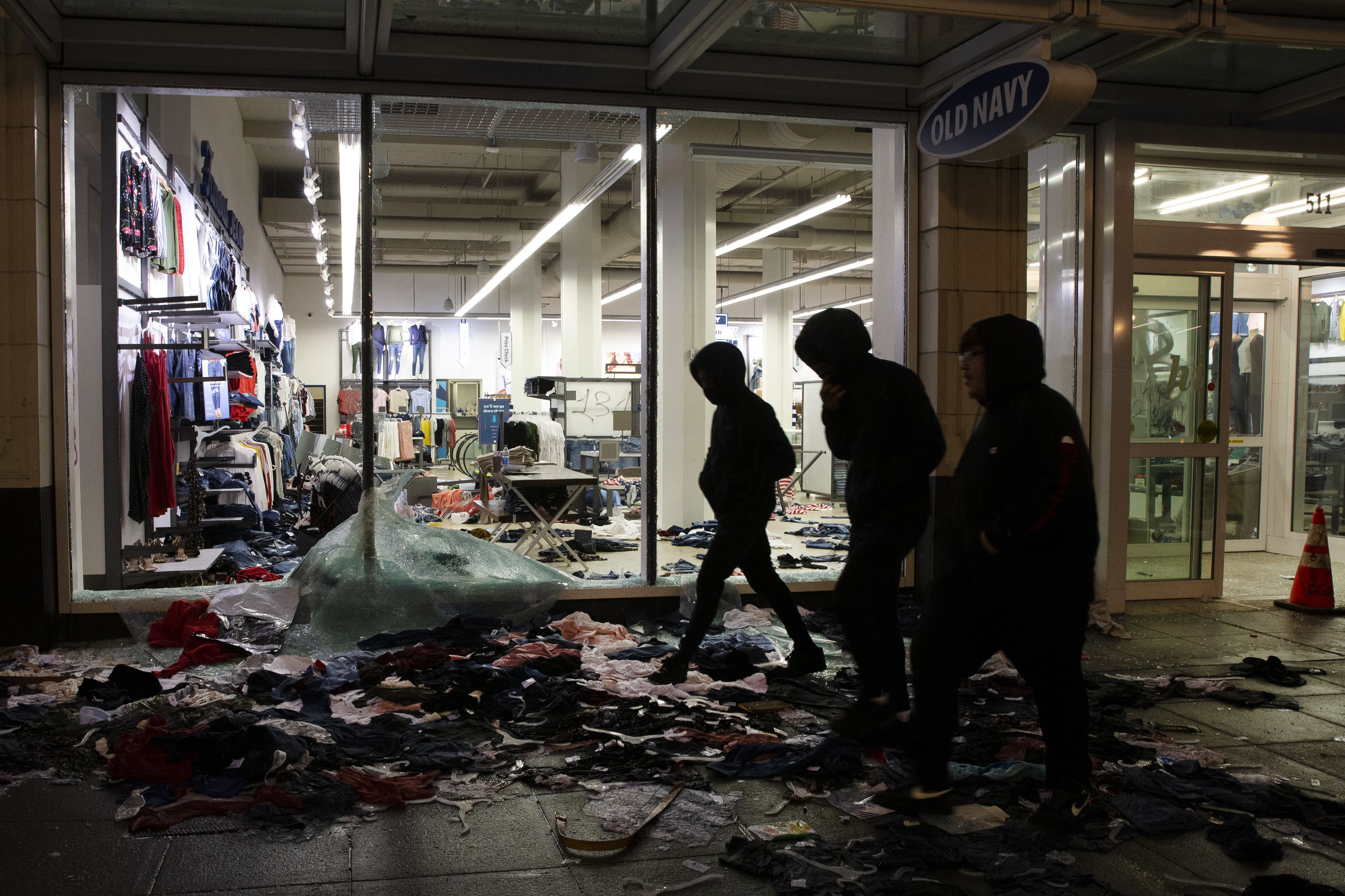 People walk past a looted store in Seattle on May 30.