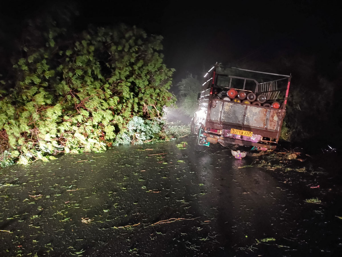 A truck loaded with oxygen cylinders is stuck beside trees that fell due to the impact of Cyclone Tauktae in Gujarat state, India on May 17.
