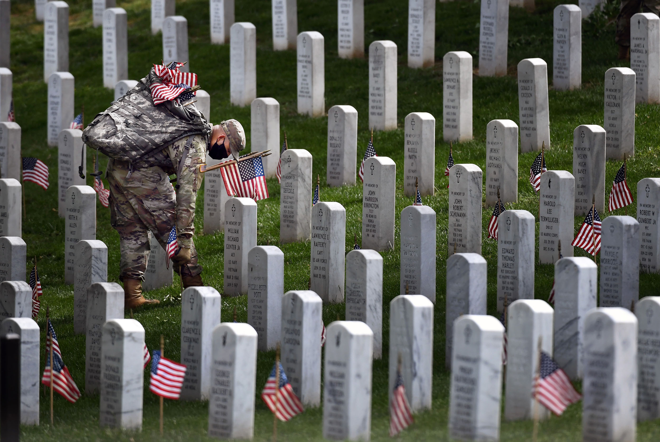 A member of the military place flags near headstones at the Arlington National Cemetery for Memorial Day in Arlington, Virginia on Thursday, May 21.