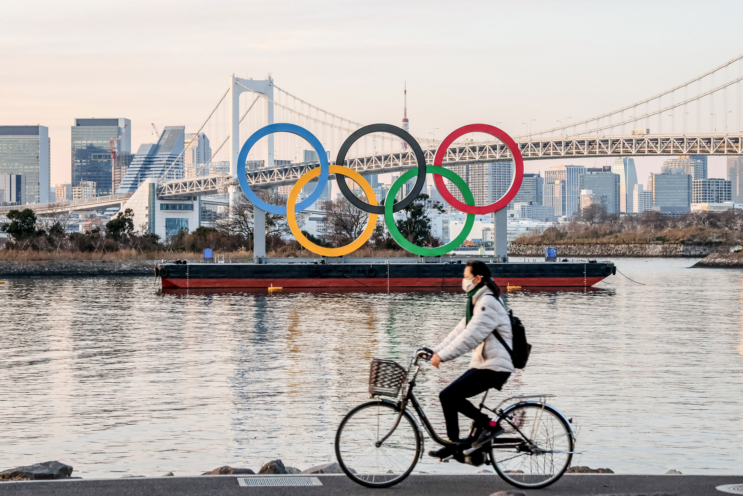 A person rides by the Olympic symbol in Tokyo on January 25.