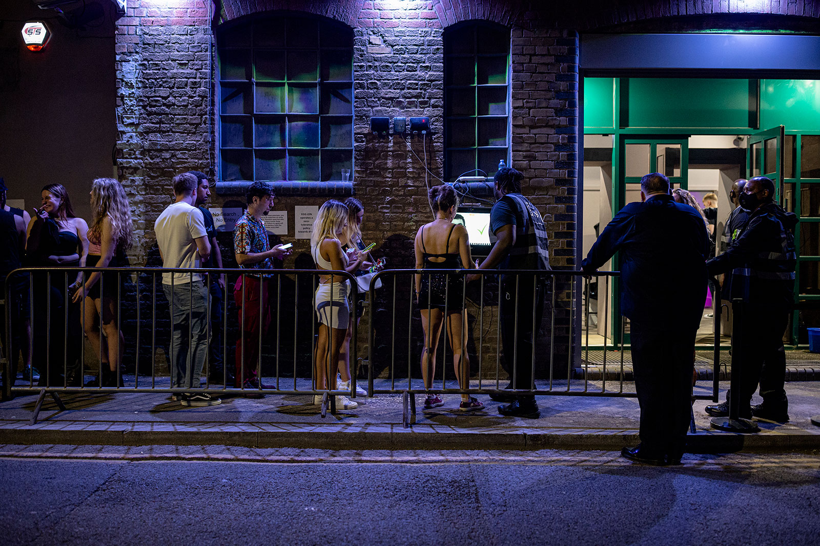 People wait in line to get into a nightclub in London, England, on July 19.