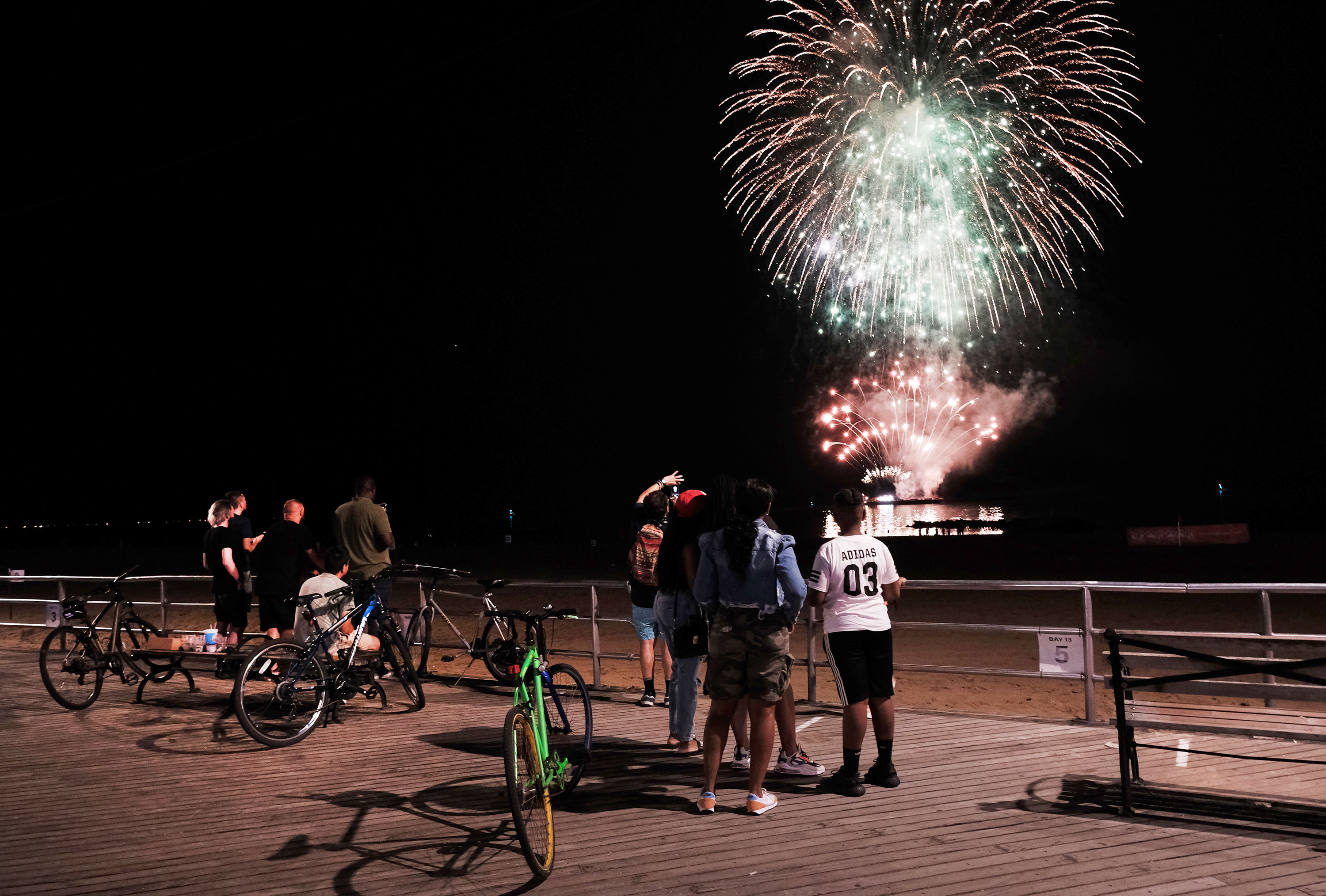 A small group of people watch a fireworks show at Coney Island on June 29 in New York.