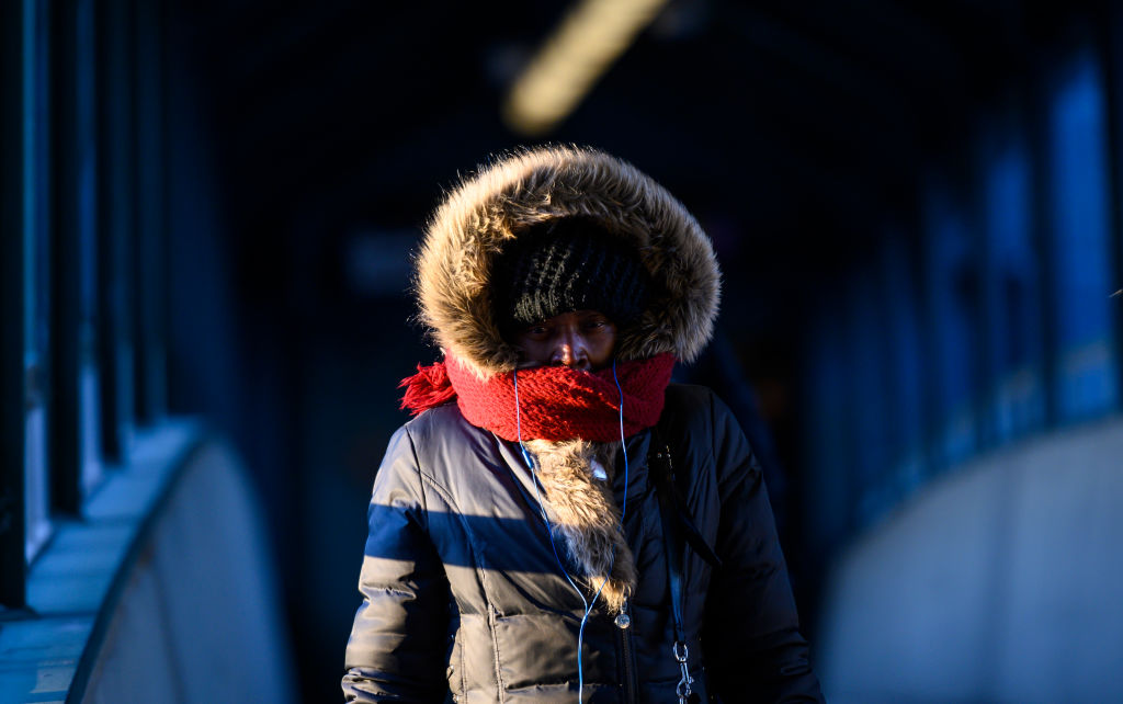 A woman walks on a pedestrian bridge with her face covered to protect from the cold on Jan. 31, 2019 in New York City.